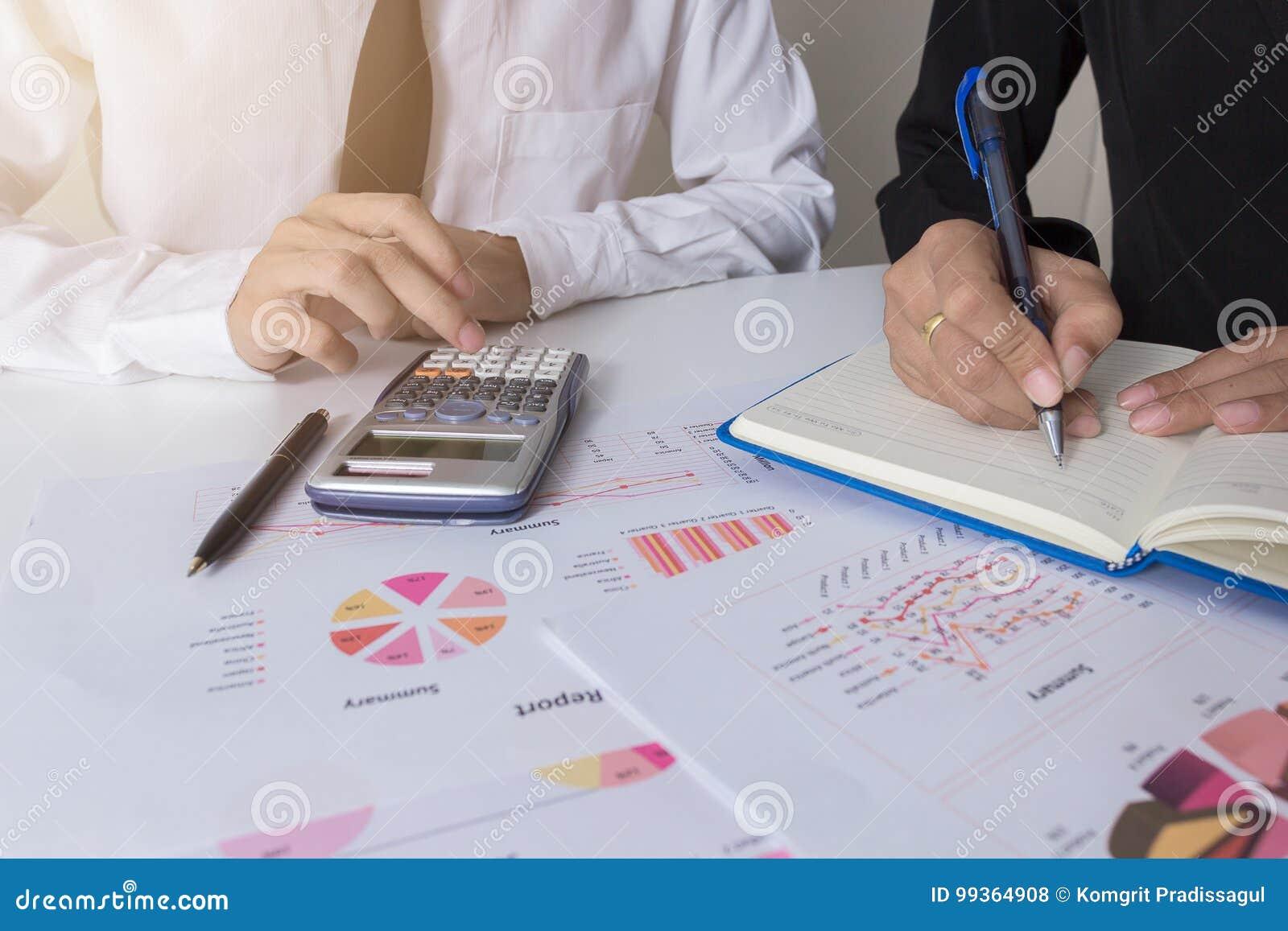 两个商人同事谈论计划与在办公室桌上的财政图表数据与膝上型计算机,概念co工作,企业mee