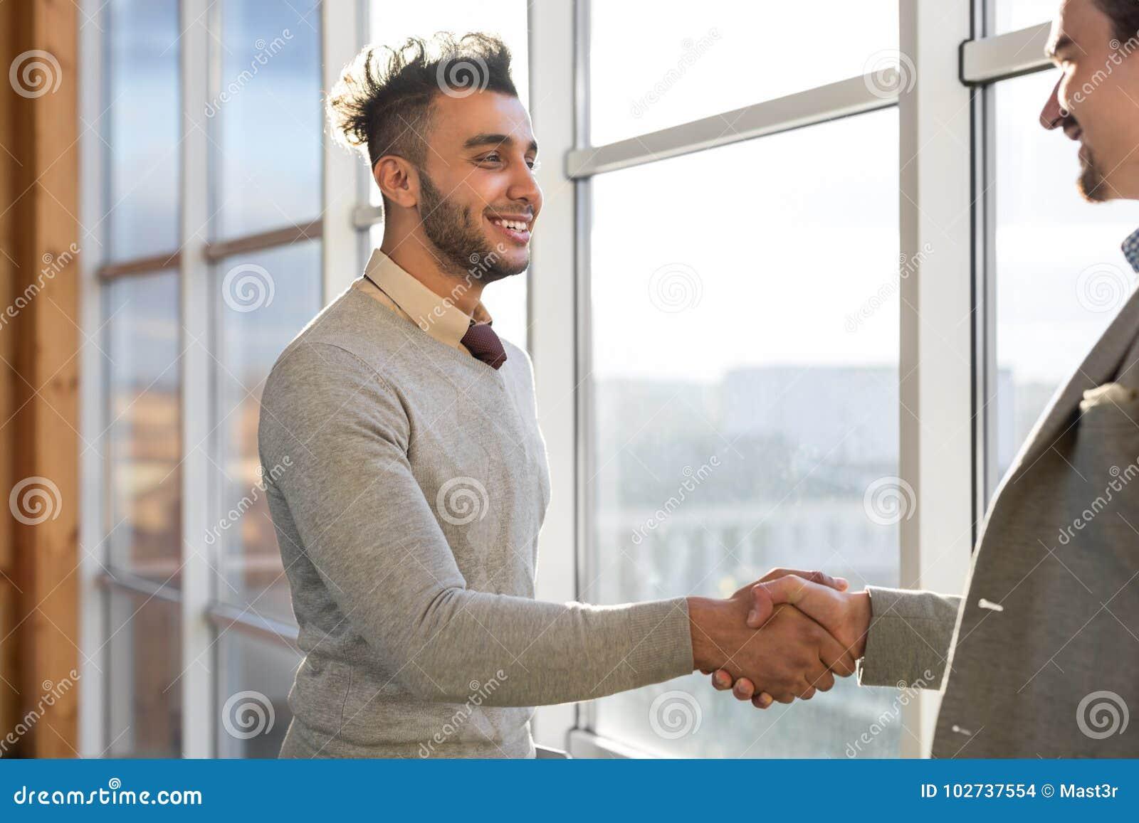 两个商人震动手协议Coworking中心企业队工友在前面大全景窗口里站立