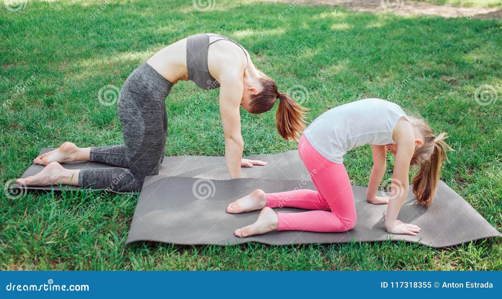 两个女孩在carimate站立并且拿着他们的后面弯曲 他们在那个姿势平衡 集中女孩