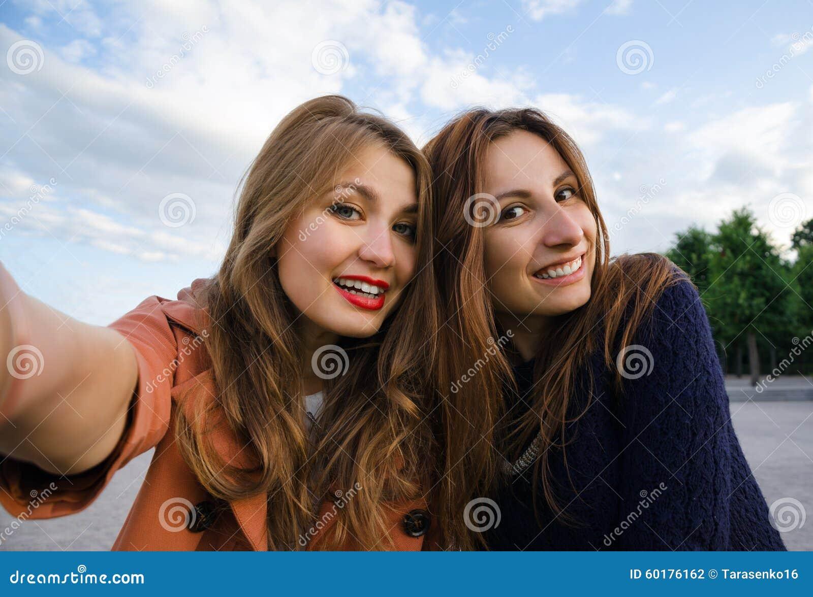 库存照片: 两个女朋友微笑做selfie图片