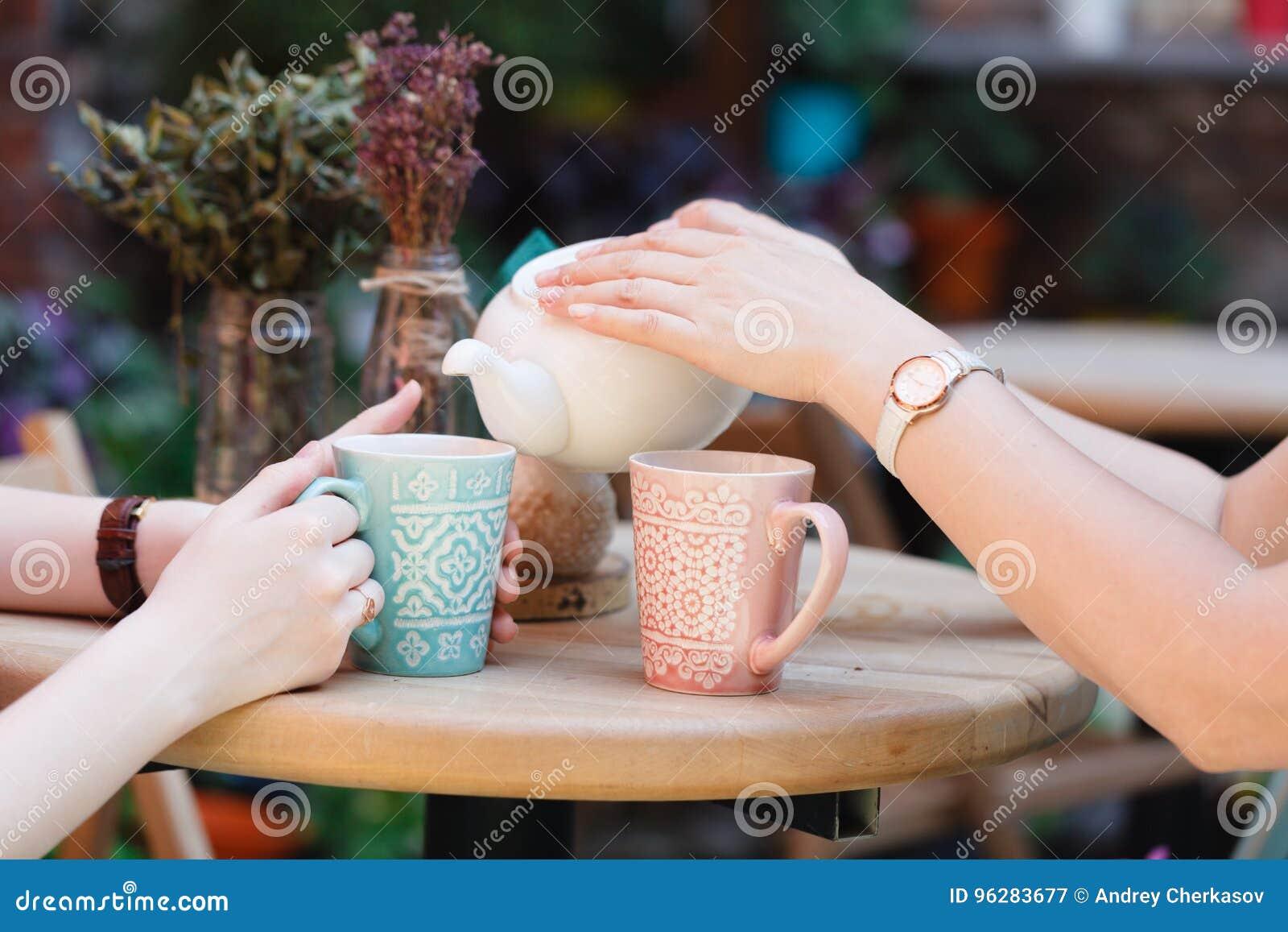 两个女朋友谈并且喝在咖啡馆的茶,户外