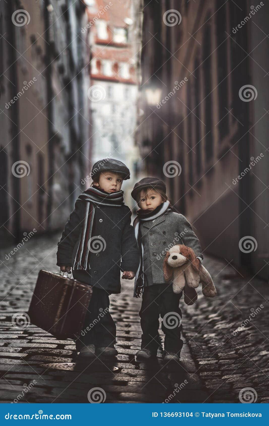 两个孩子、男孩兄弟、运载的手提箱和狗玩具,旅行在单独城市