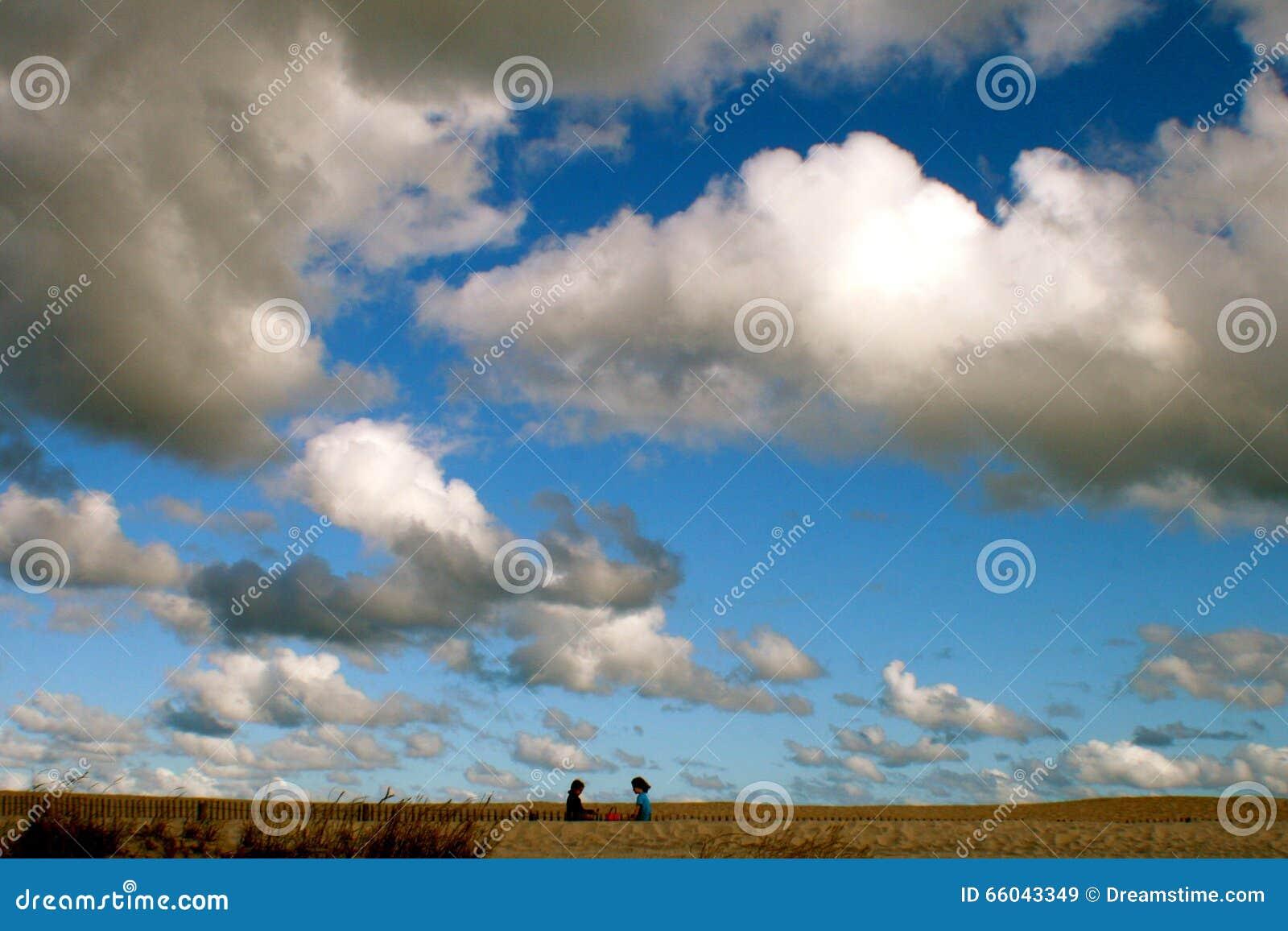 两个孩子谈话在与大天空的海滩在他们上