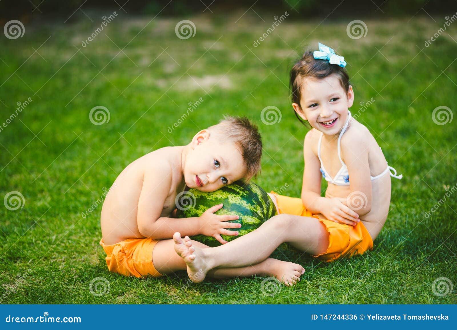 两个孩子,白种人兄弟和姐妹,坐绿草在房子后院和拥抱大鲜美甜西瓜