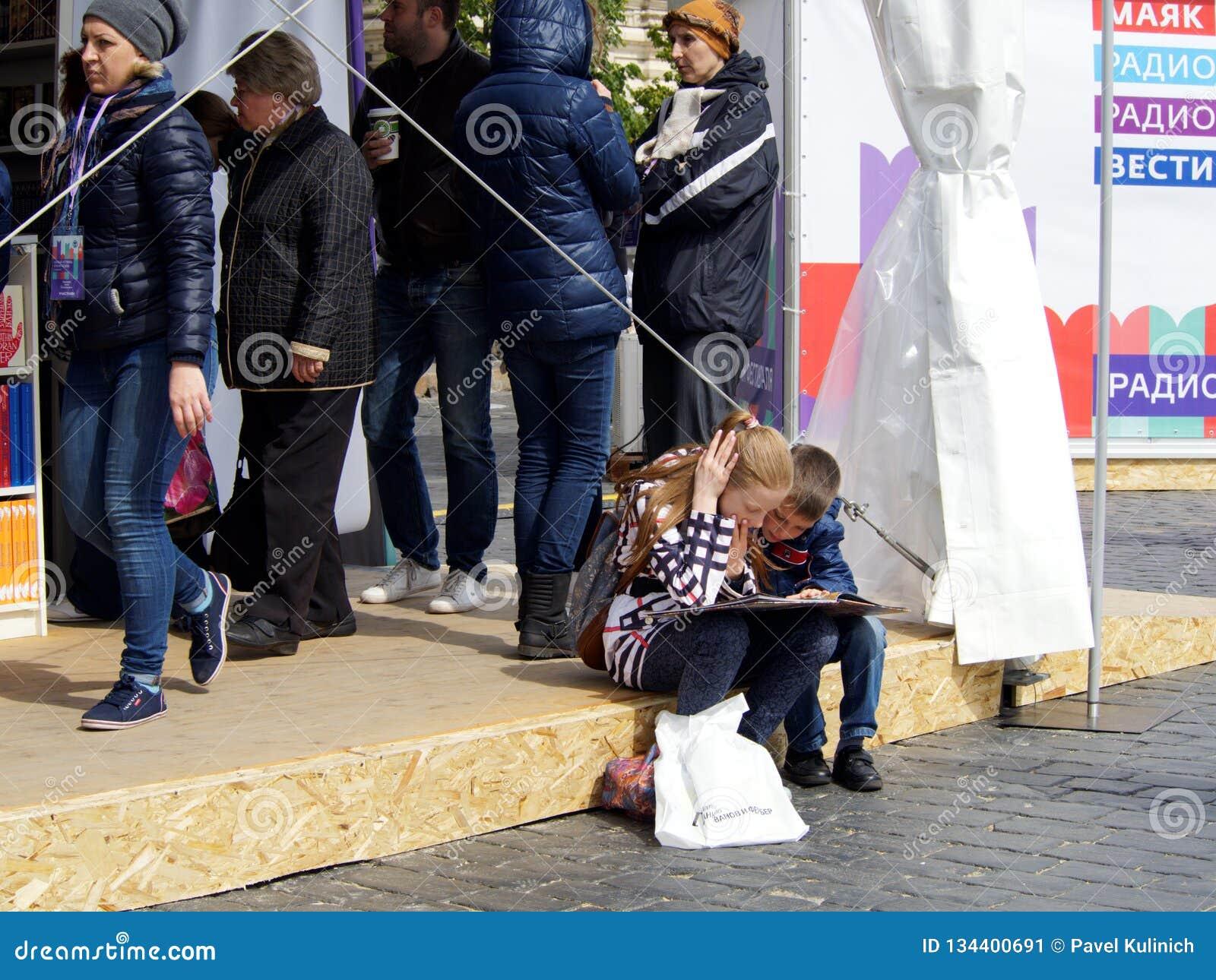 两个孩子-女孩和男孩看与兴趣的开放书