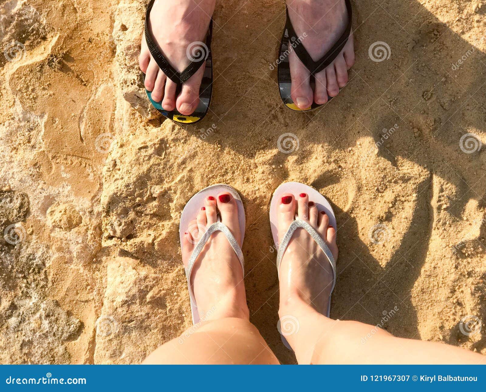 两个对有修指甲的在拖鞋,与手指的一只脚男性和女性腿在一个石含沙地板,地球上的啪嗒啪嗒的响声,是