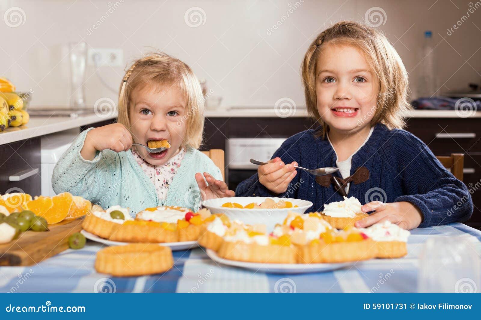 两个小女孩用奶油色点心