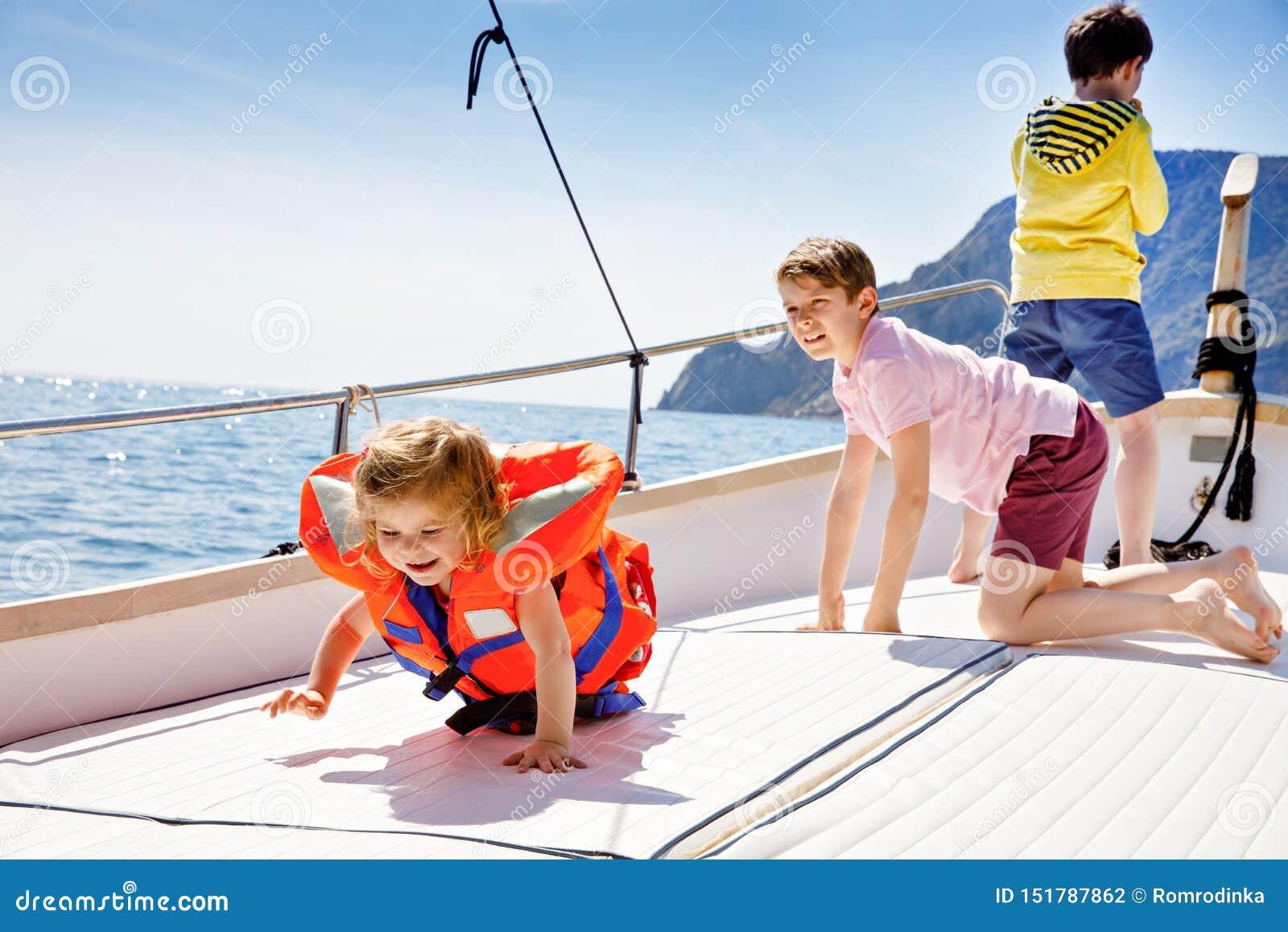 两个小孩男孩和享受帆船旅行的小孩女孩 在海洋或海的家庭度假在好日子 ??
