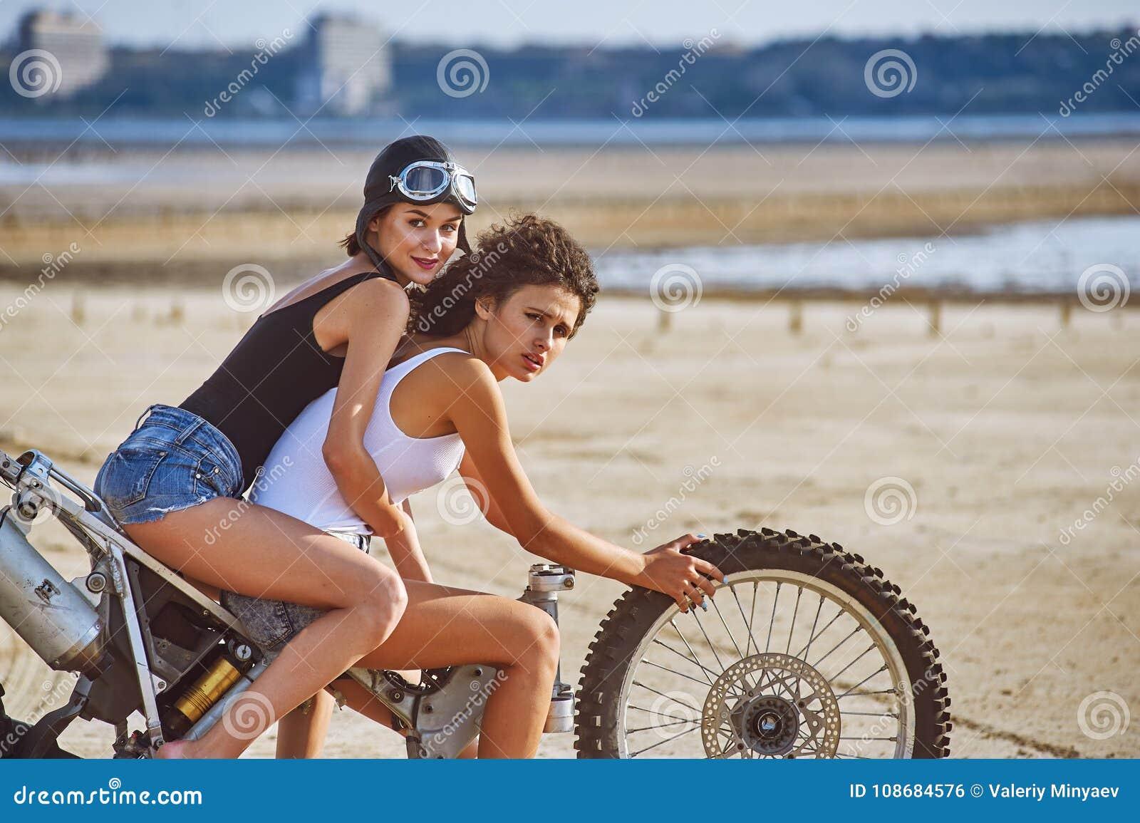 两个少妇获得使用在一辆被拆卸的摩托车的乐趣