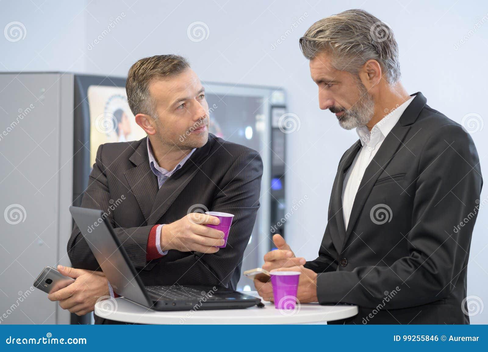 两个年轻商人喝咖啡使用便携式计算机