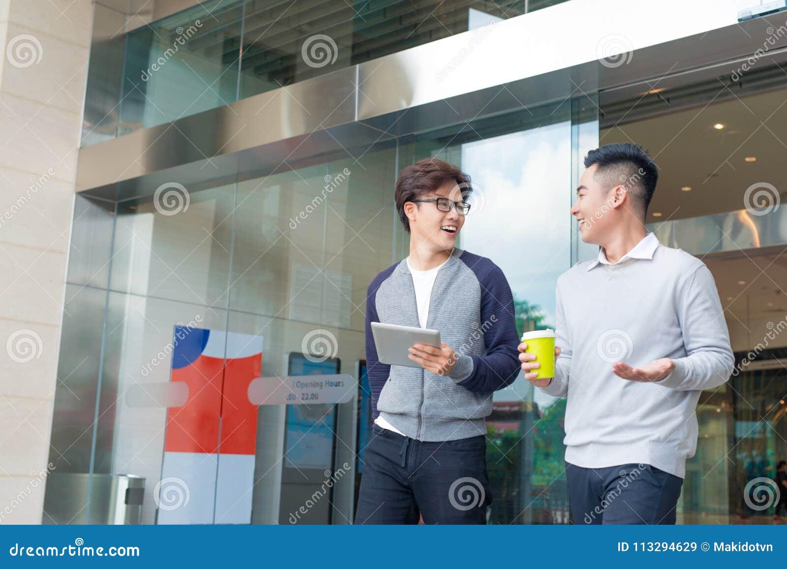 两个微笑的商人走和谈话在城市