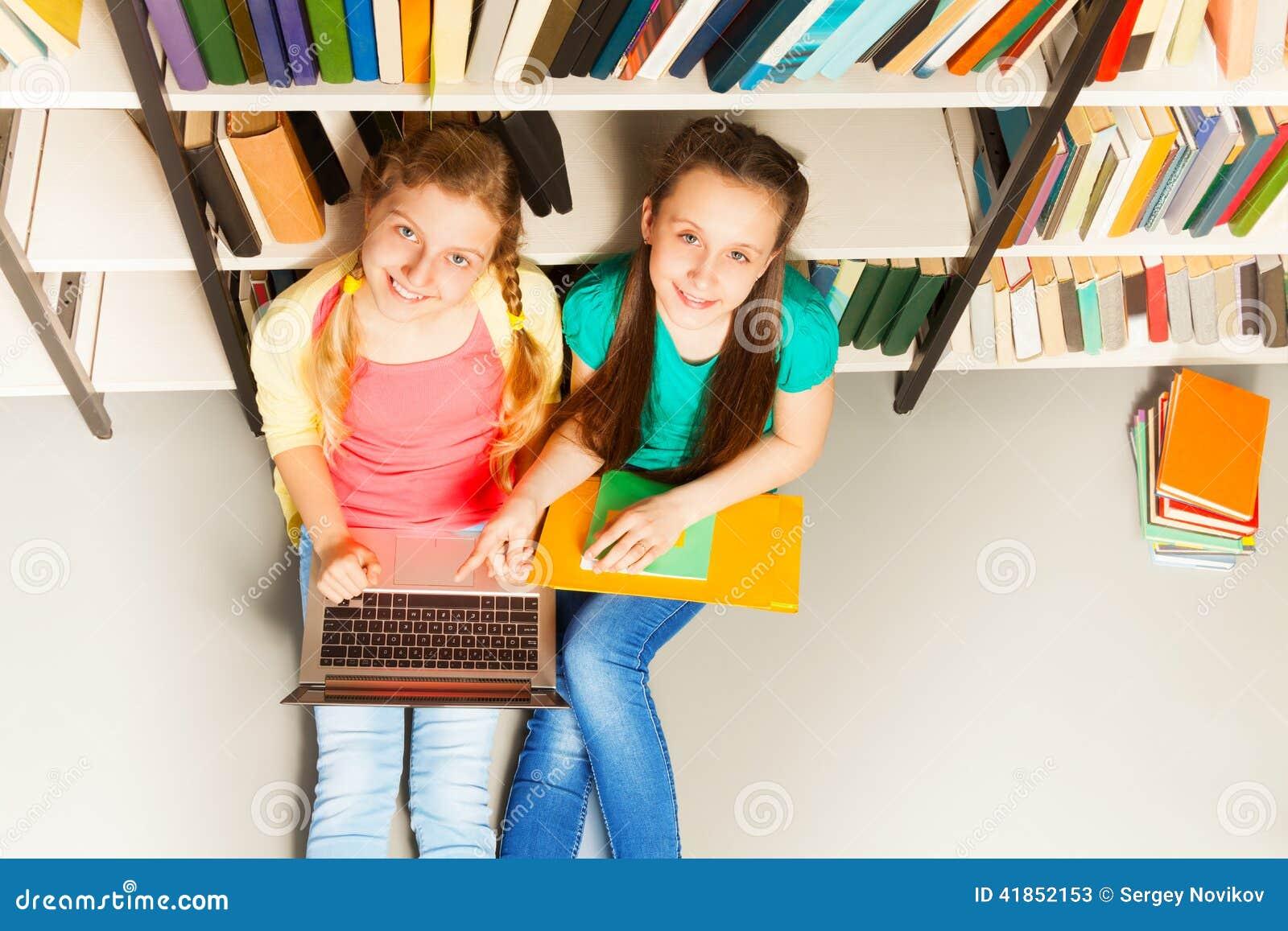 两个微笑的女孩画象从上面在图书馆里