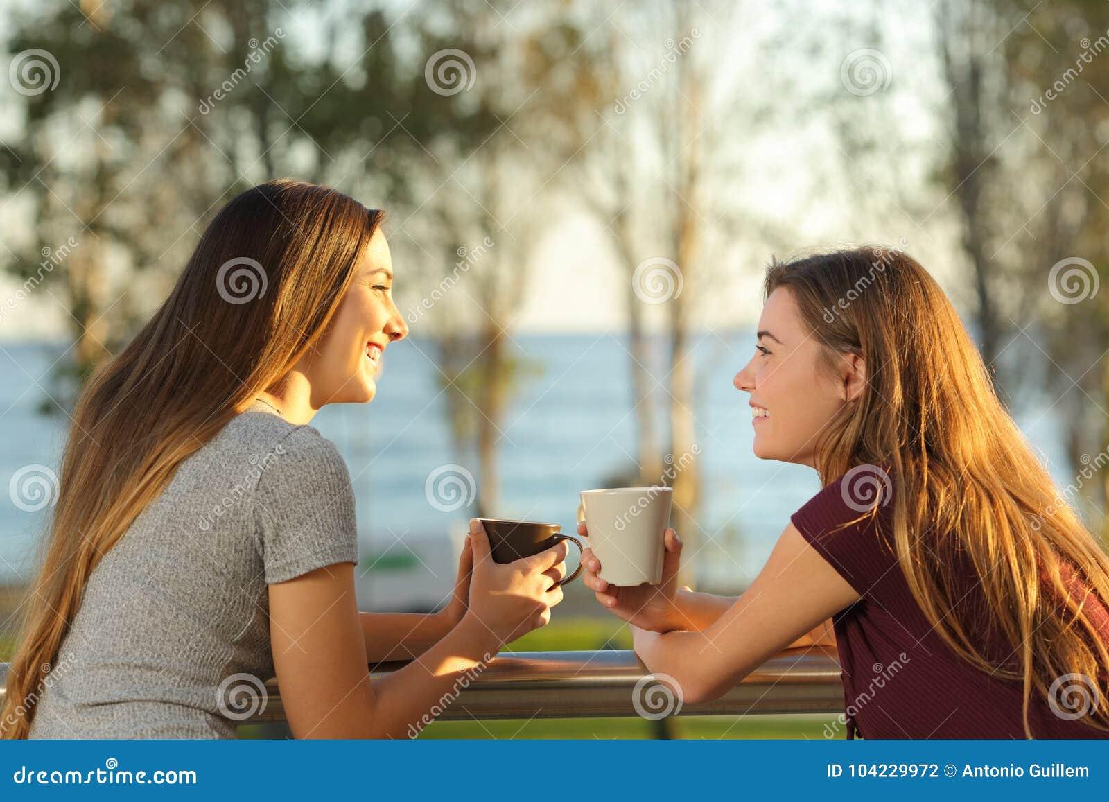 两个愉快的朋友谈话户外在阳台上