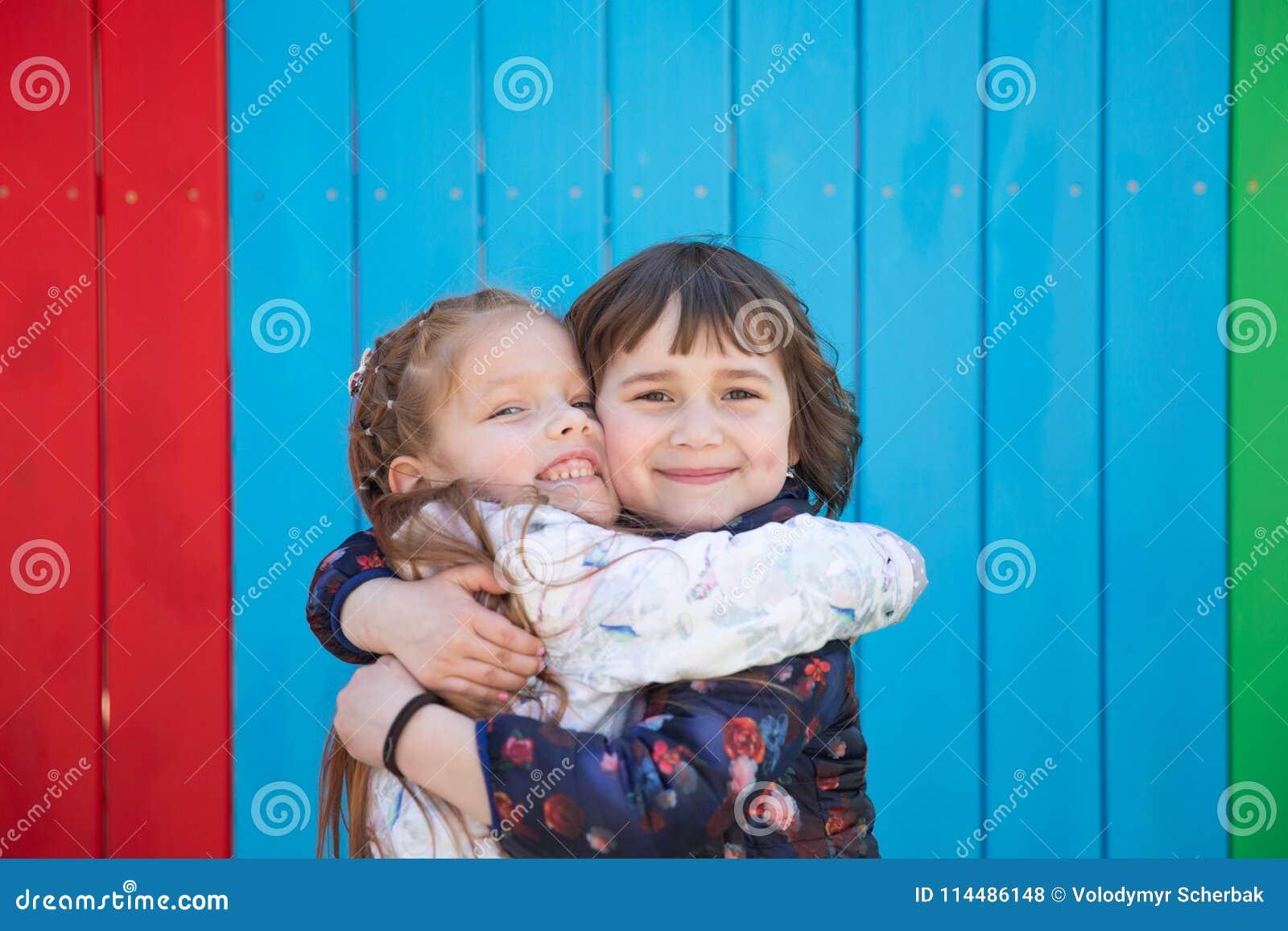 两个拥抱的逗人喜爱的小女孩室外画象