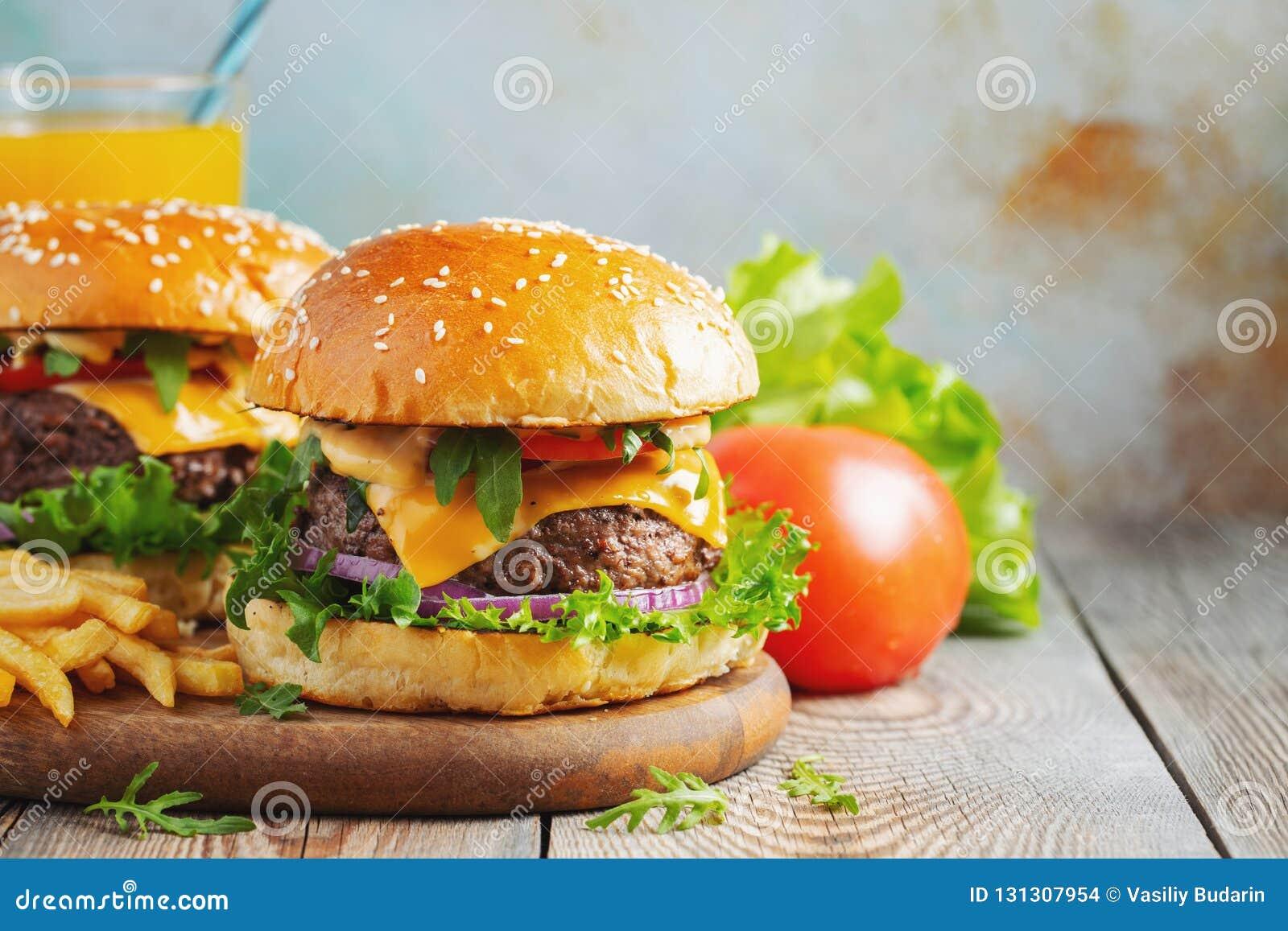 两个新鲜的自创汉堡用油煎的土豆和橙汁过去在一张木桌上 复制空间