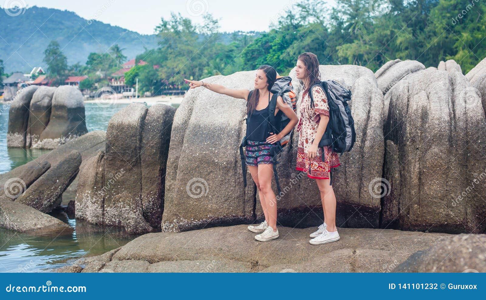 两个旅客放松在岩石的妇女背包徒步旅行者在晴朗的海滩