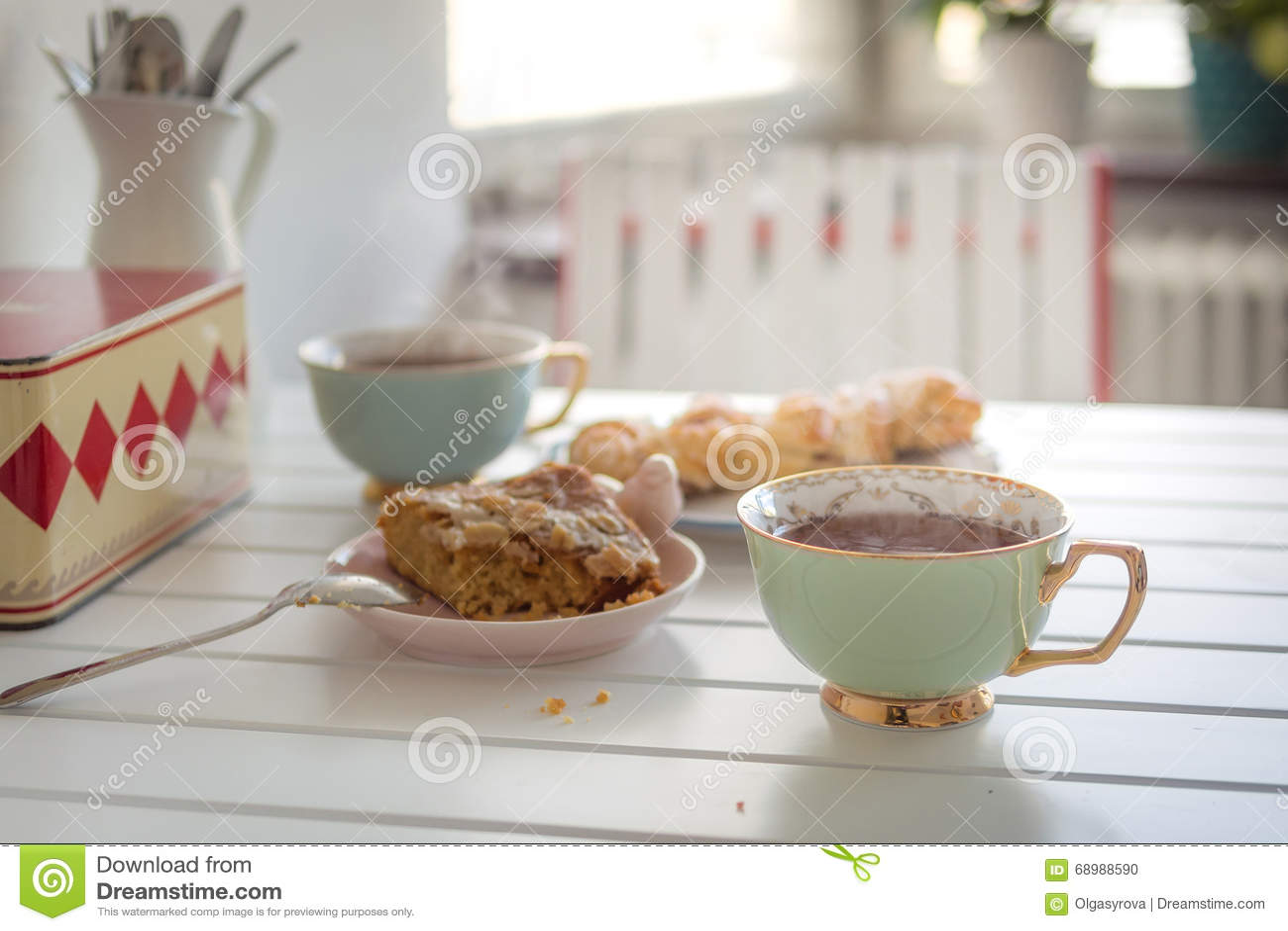 两个杯子与两个蛋糕的热的茶在一张白色桌上