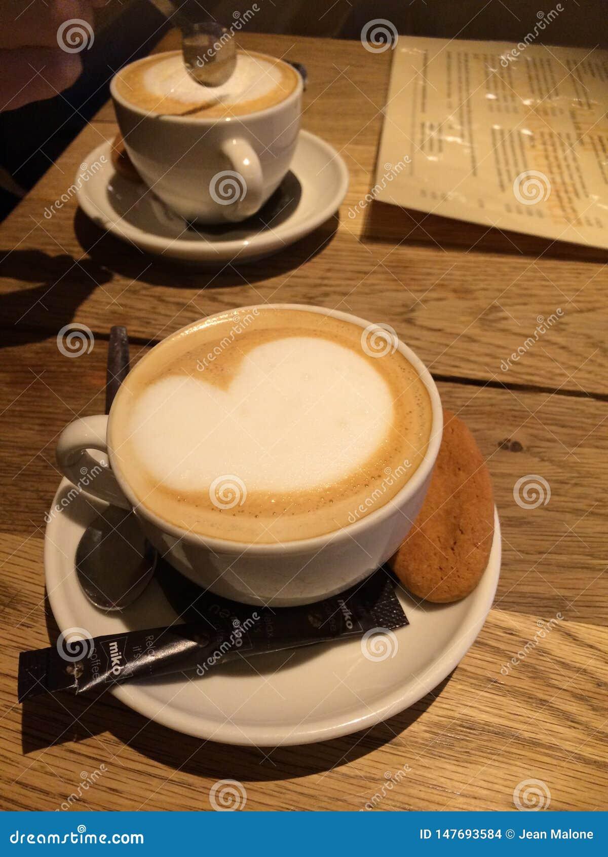 两个杯子在一张木桌上的热奶咖啡与泡沫的心脏和饼干