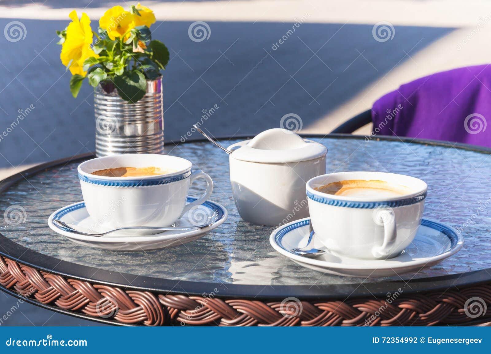 两个杯子在玻璃桌上的热奶咖啡立场