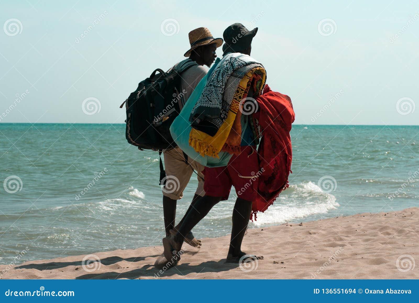 两个深色皮肤的人,走沿岸的海滩客商