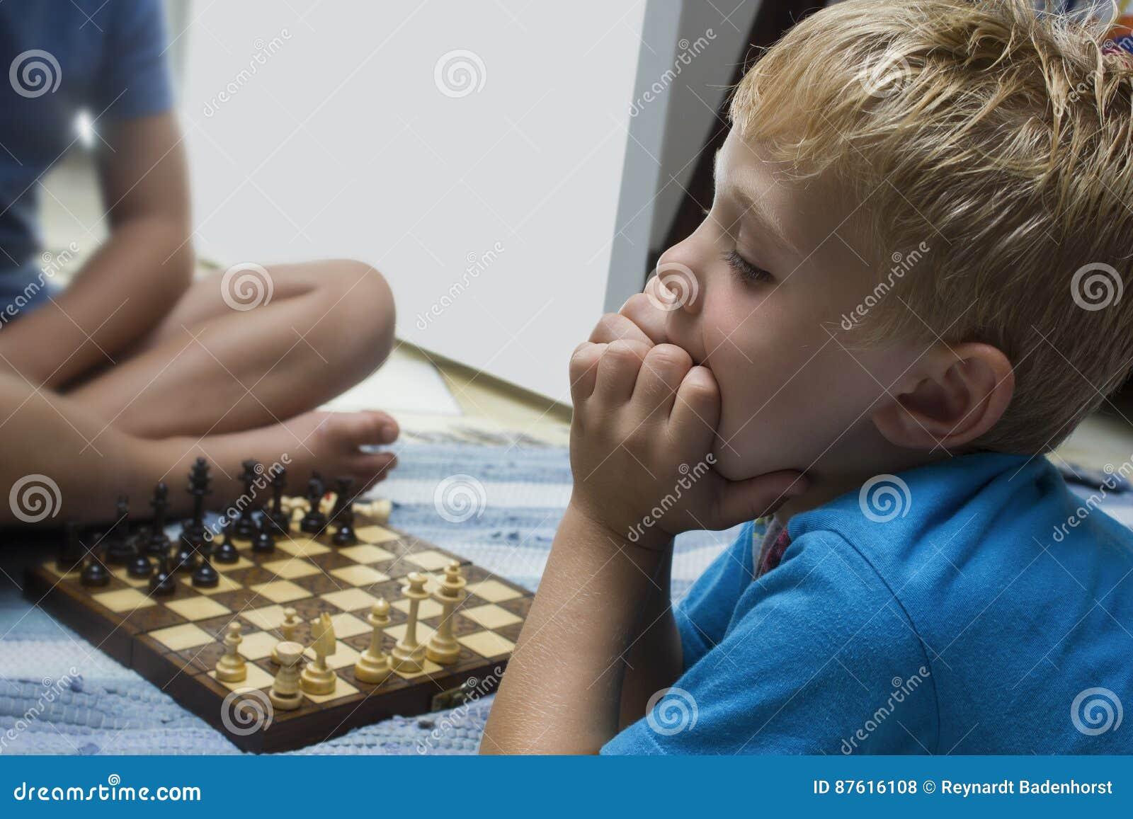 两个男孩打棋盘比赛的和苦苦思索这一个的男孩非常