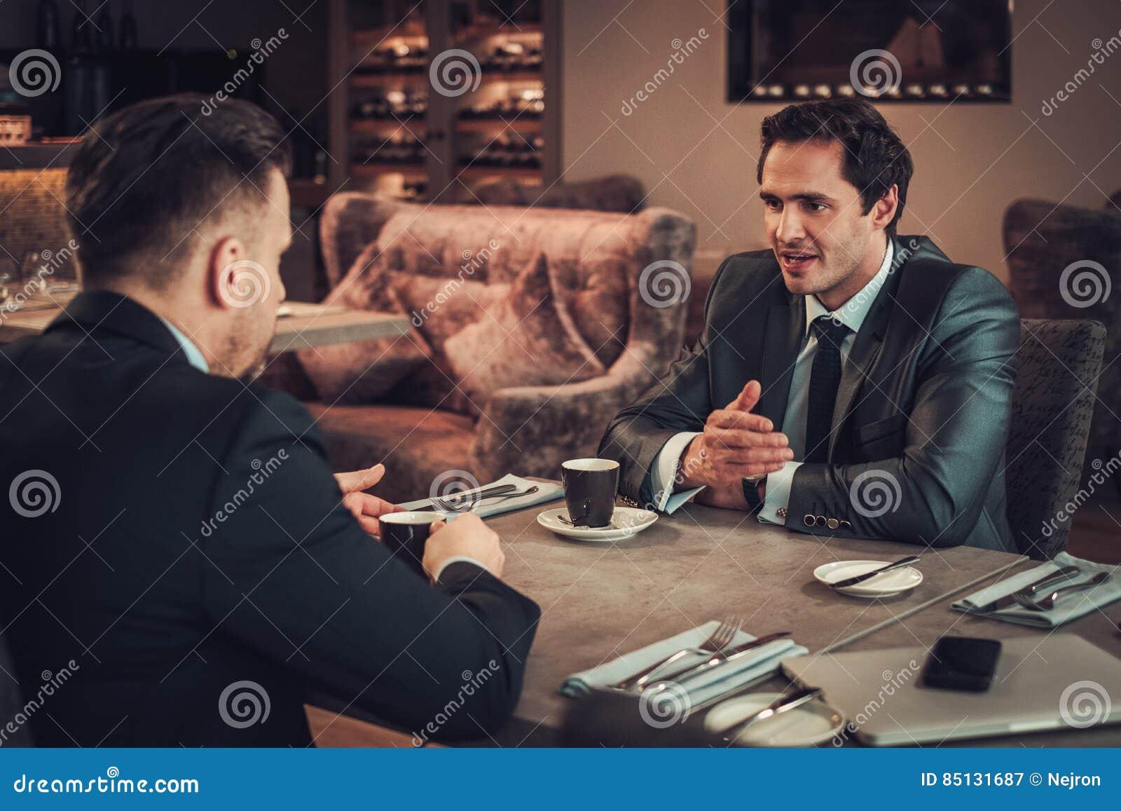 两个确信的商人有工作午餐在餐馆