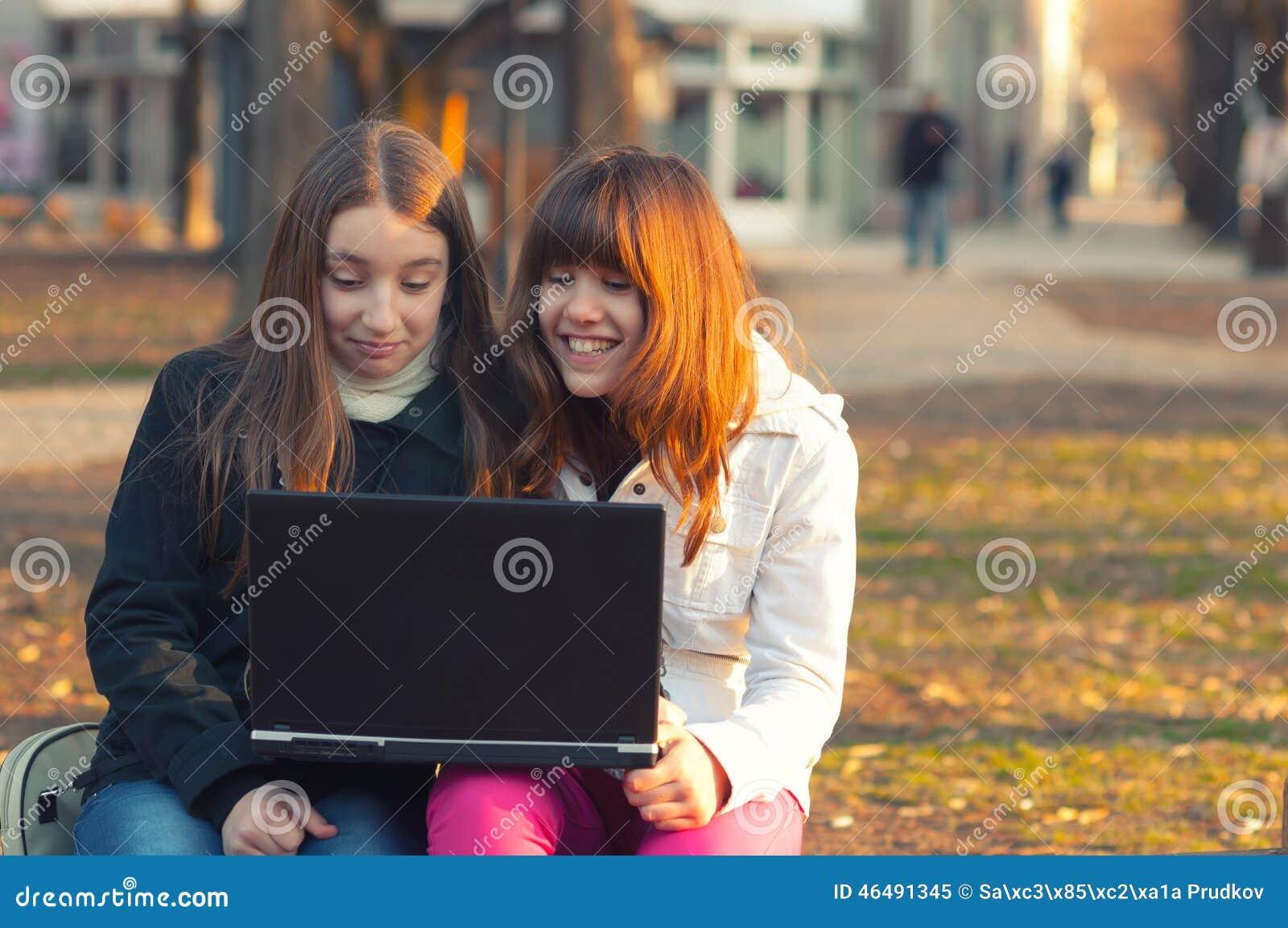 两个美丽的十几岁的女孩获得与笔记本的乐趣在公园