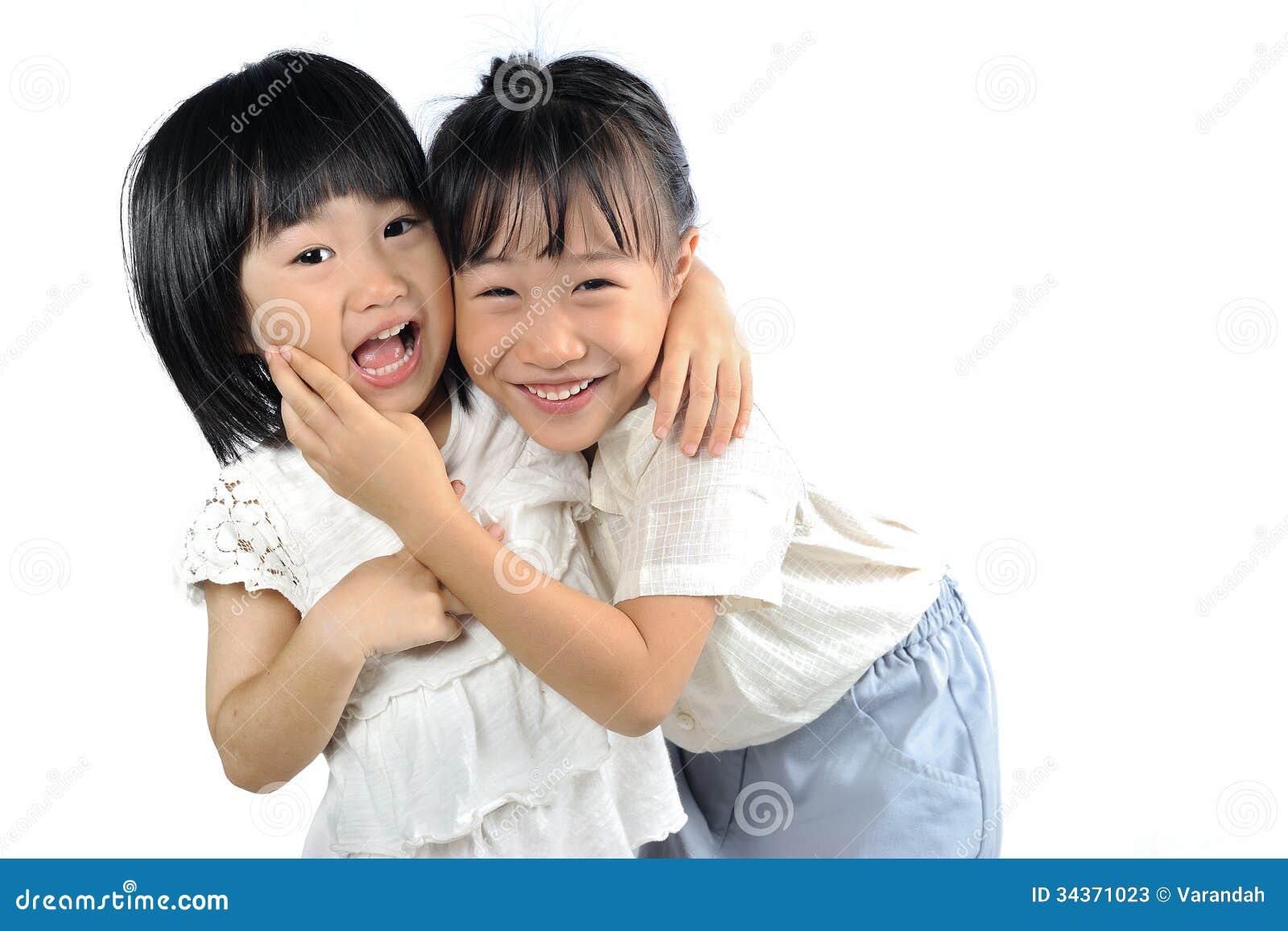 亚州爱性_两个在白色背景隔绝的愉快亚洲妹拥抱,兄弟姐妹一起爱.