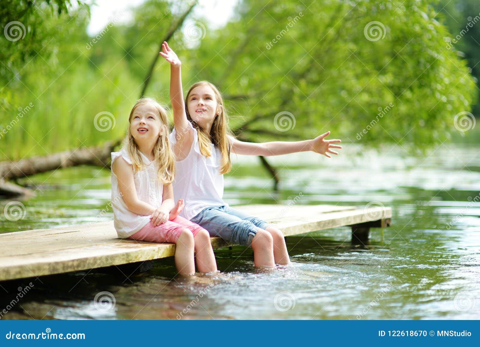 两个逗人喜爱的小女孩坐一个木平台由河或湖在水中的浸洗他们的脚在温暖的夏日