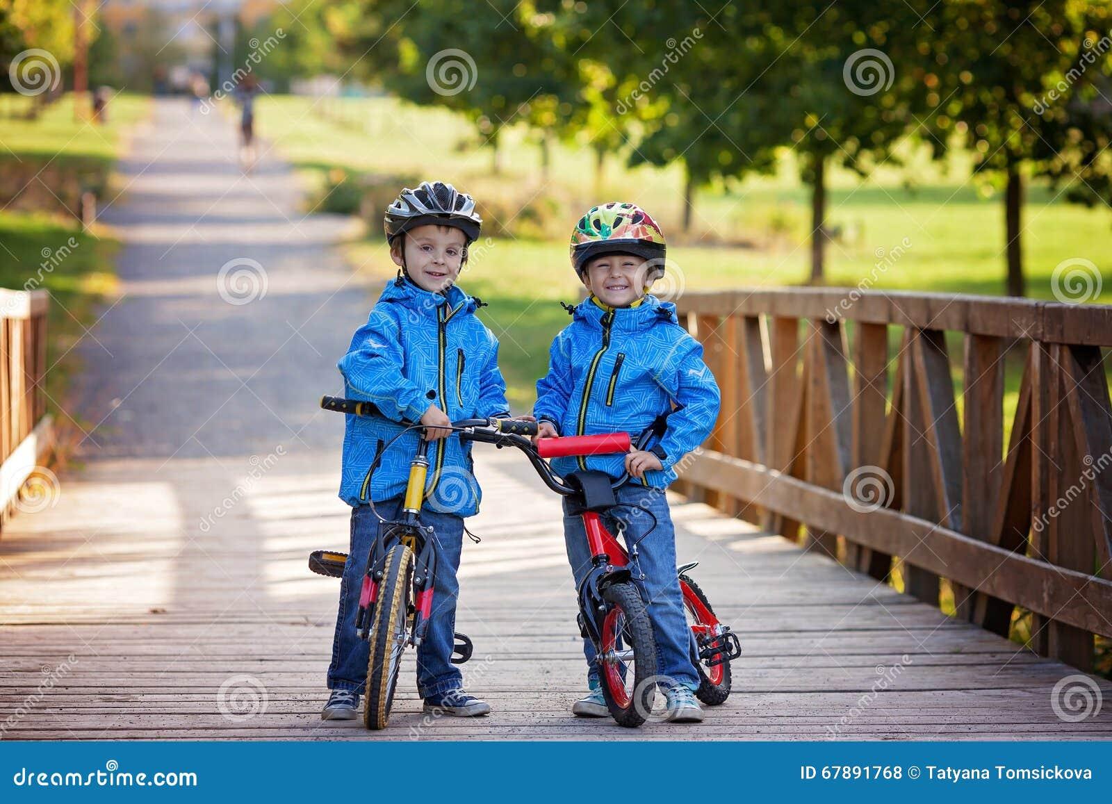 两个逗人喜爱的男孩,兄弟姐妹孩子,获得在自行车的乐趣在同水准
