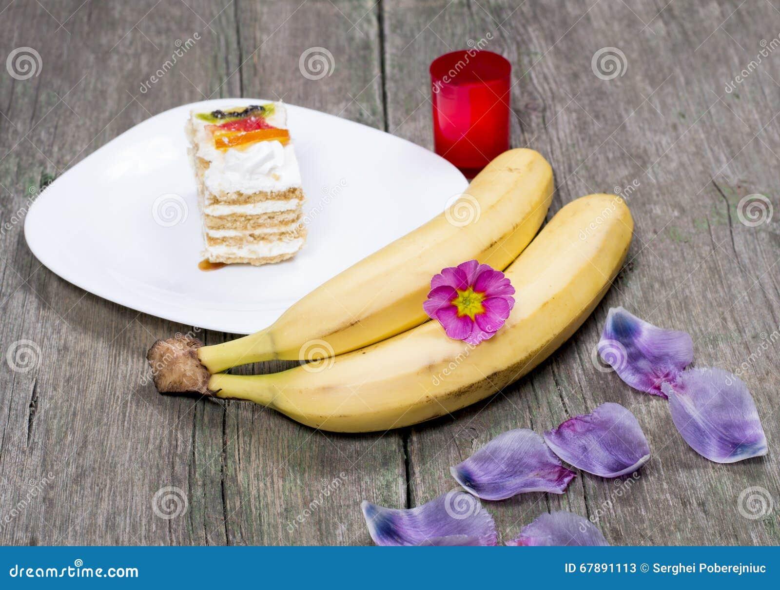 两个香蕉,有用花装饰的蛋糕的板材