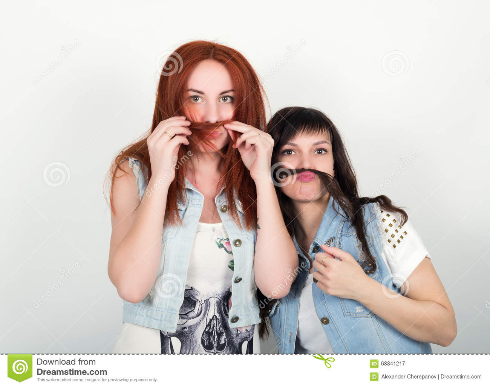 两个年轻女朋友从头发沉溺并且做鬼脸,互相做髭 做髭的少年从