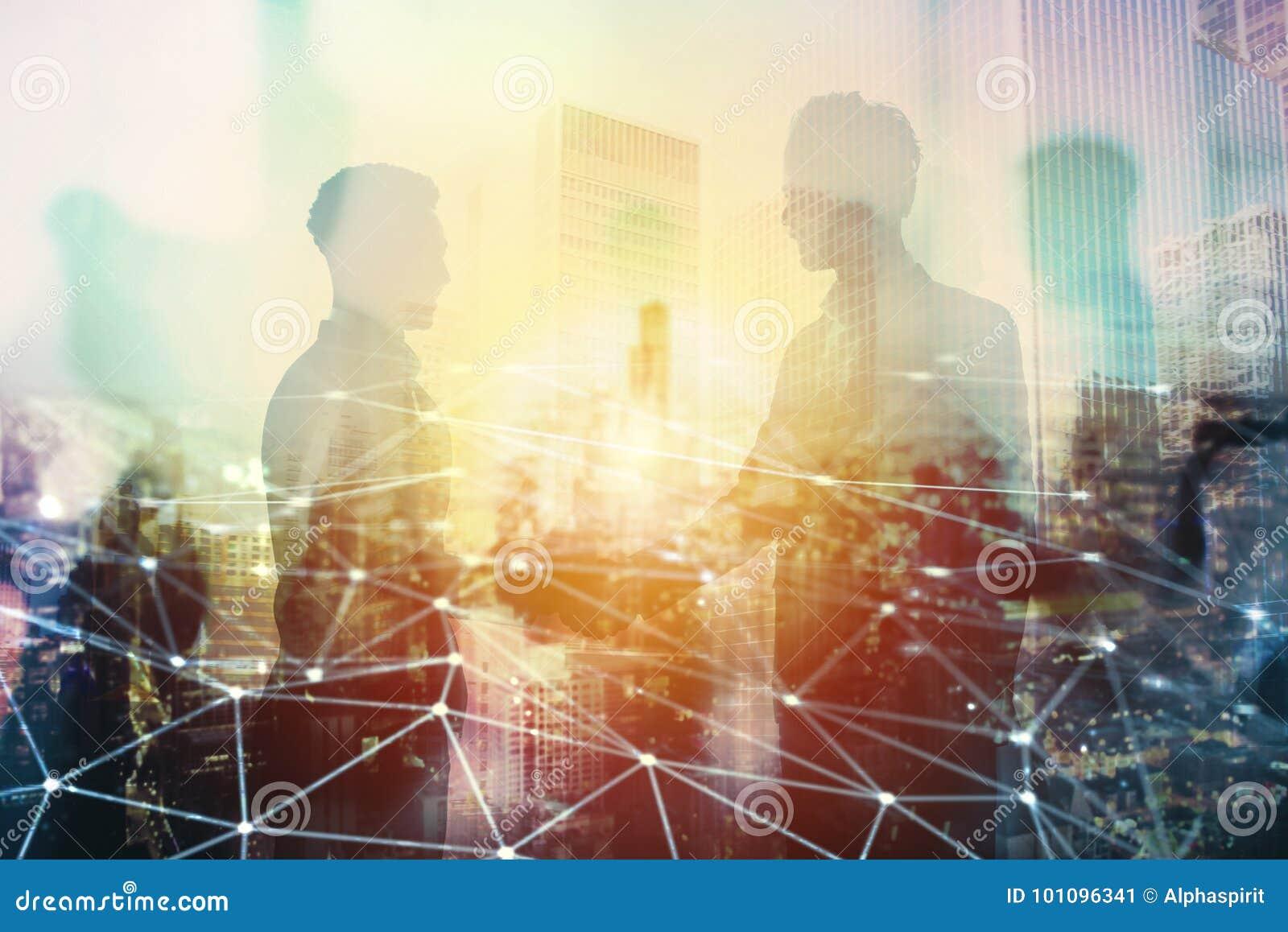 两买卖人握手在有网络作用的办公室 合作和配合的概念