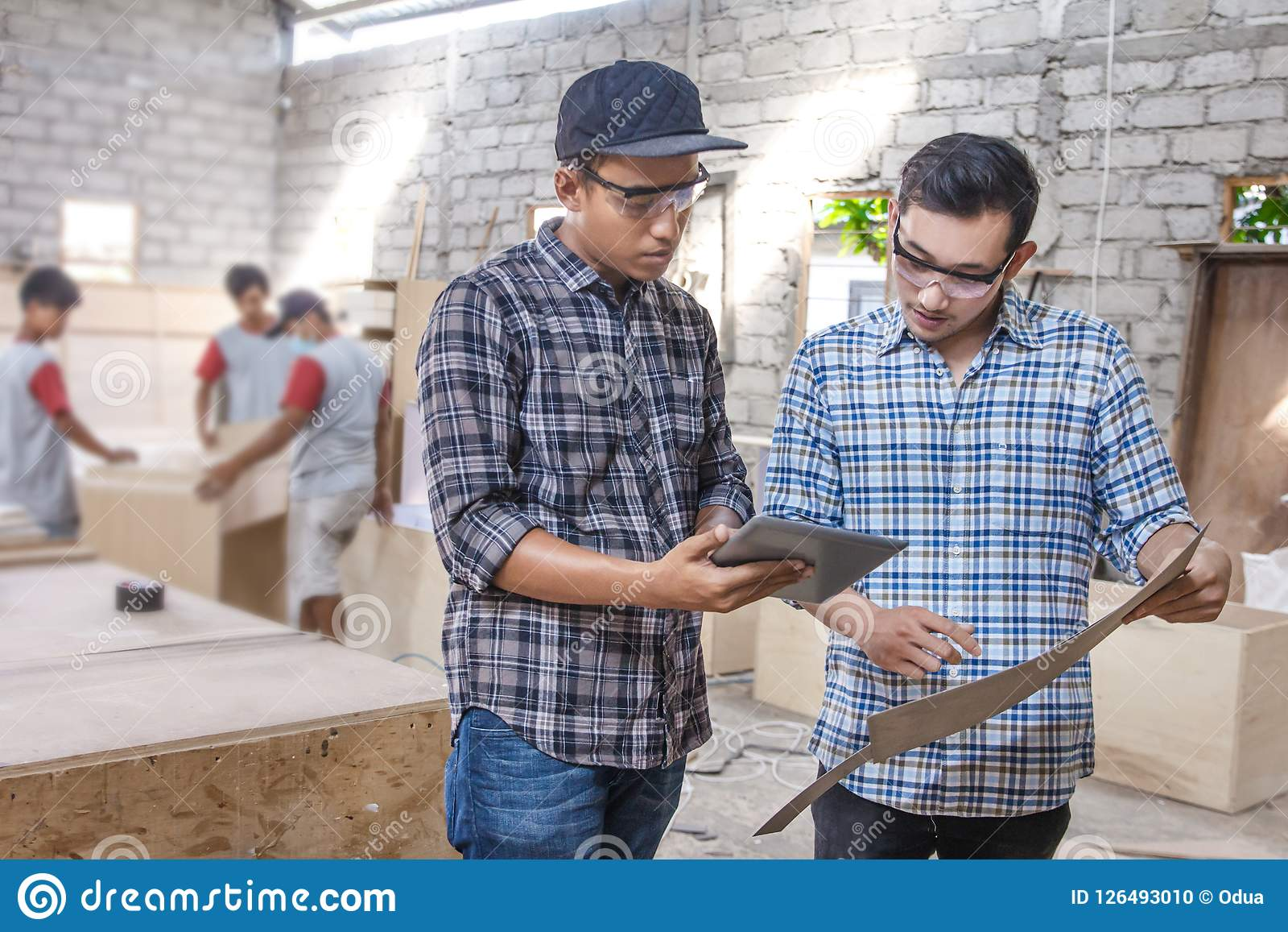 两位年轻木匠谈论关于家具材料