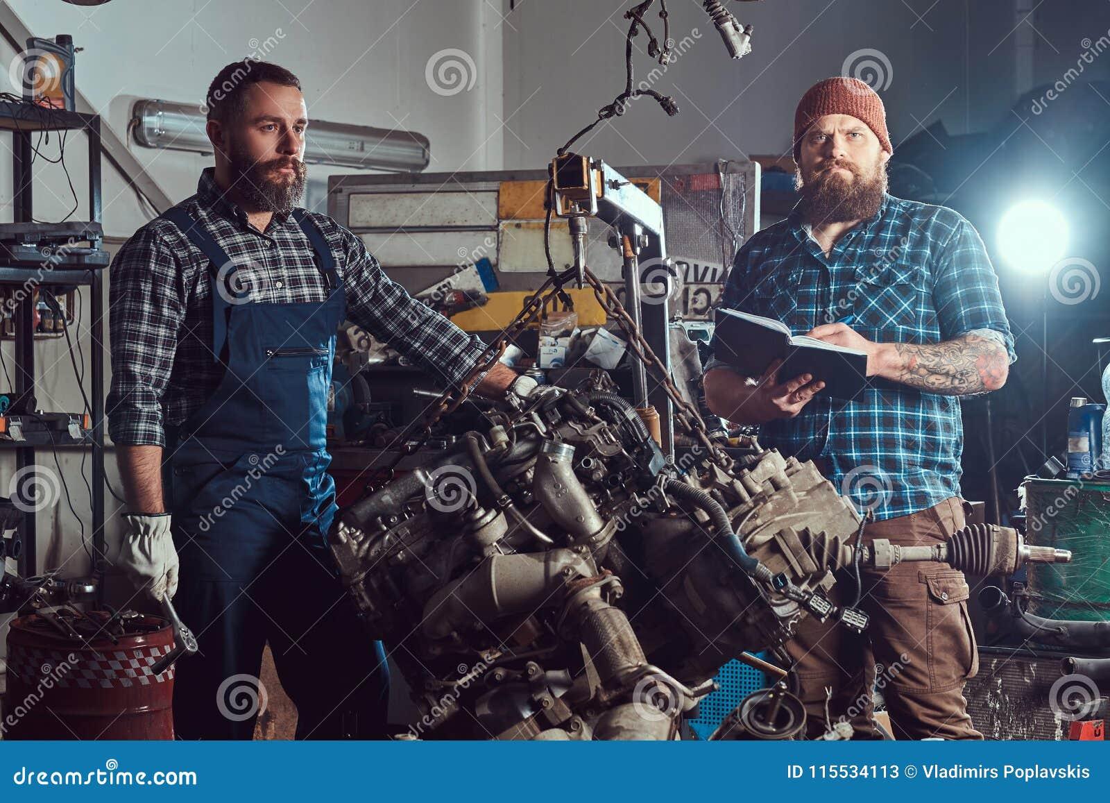 两位有胡子的技工专家修理在车库的液压悬挂被上升的发动机