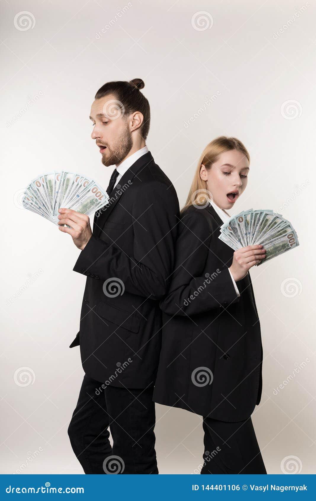 两位雇员帅哥和美丽的白肤金发的妇女紧接站立与金钱的黑衣服的在手上