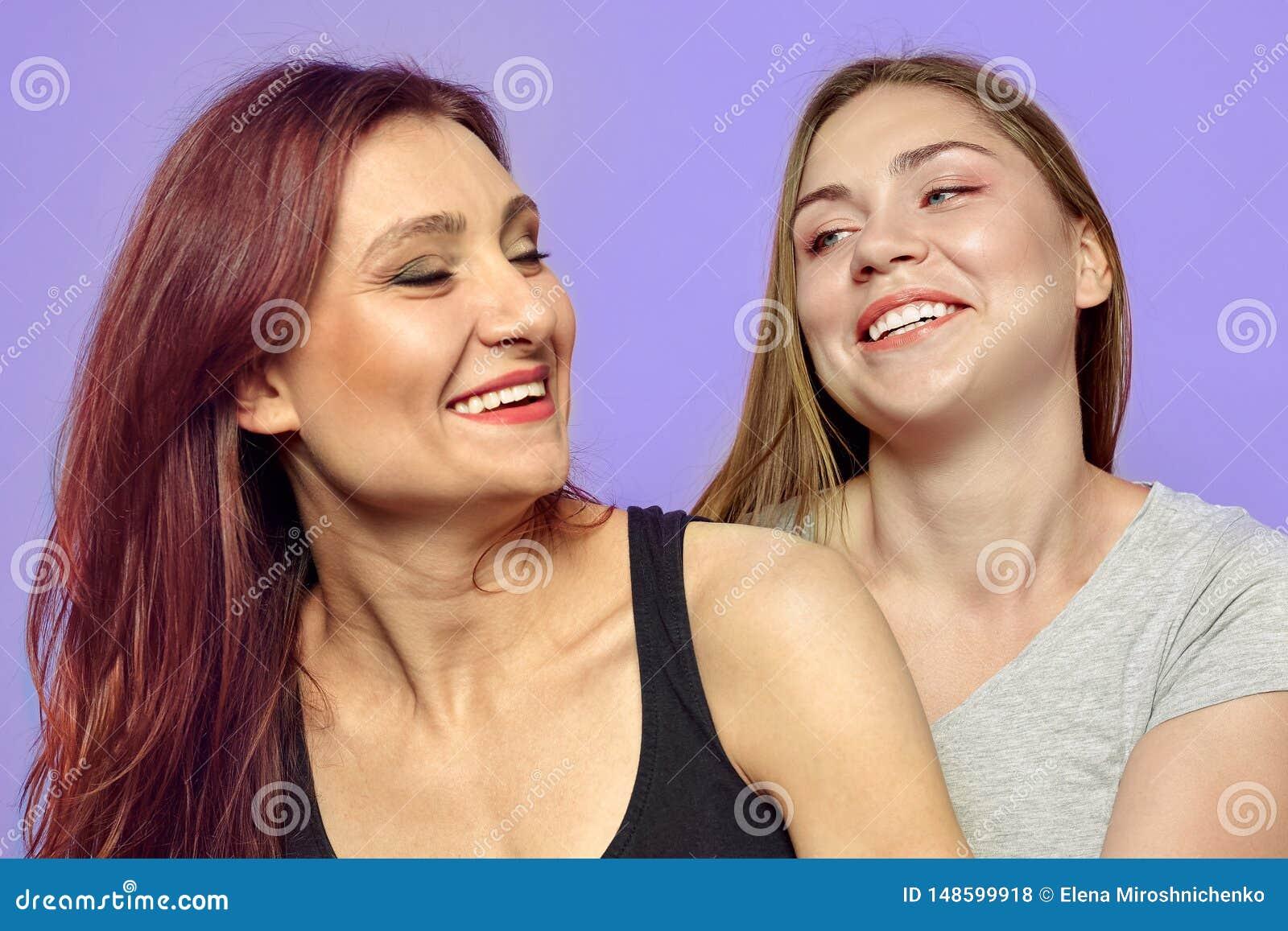两名年轻笑的妇女,一白种人白肤金发,拉丁语的另一个 美好的变化、乐趣和紧的关系,强的情感
