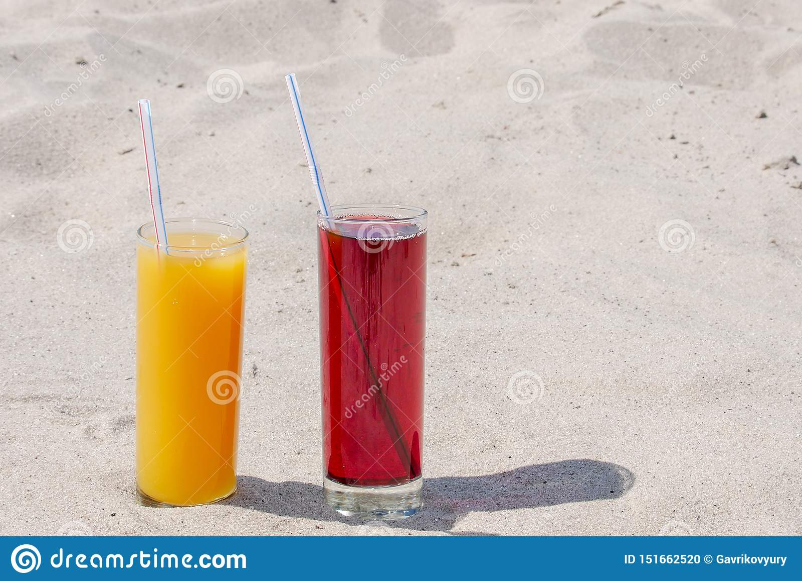 两块玻璃玻璃用芒果和樱桃汁液与小管 沙滩在一个夏日