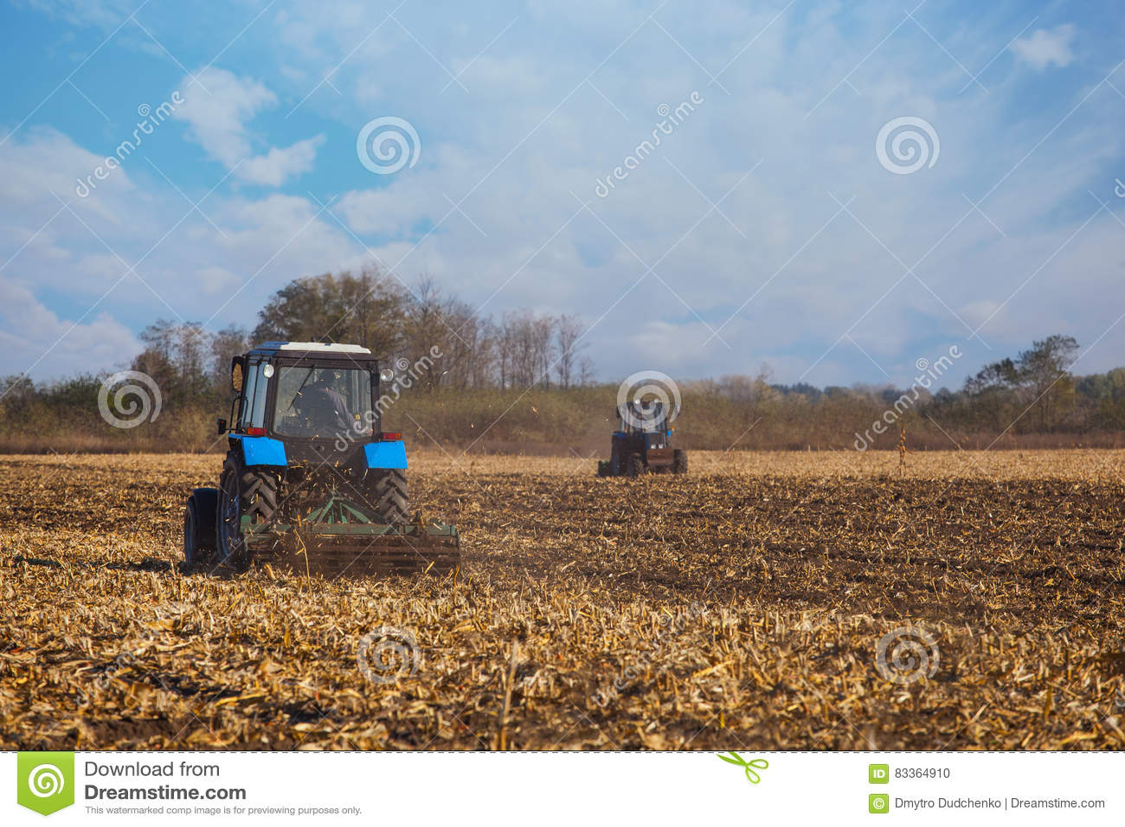 两大蓝色拖拉机犁在收获玉米庄稼以后犁了土地
