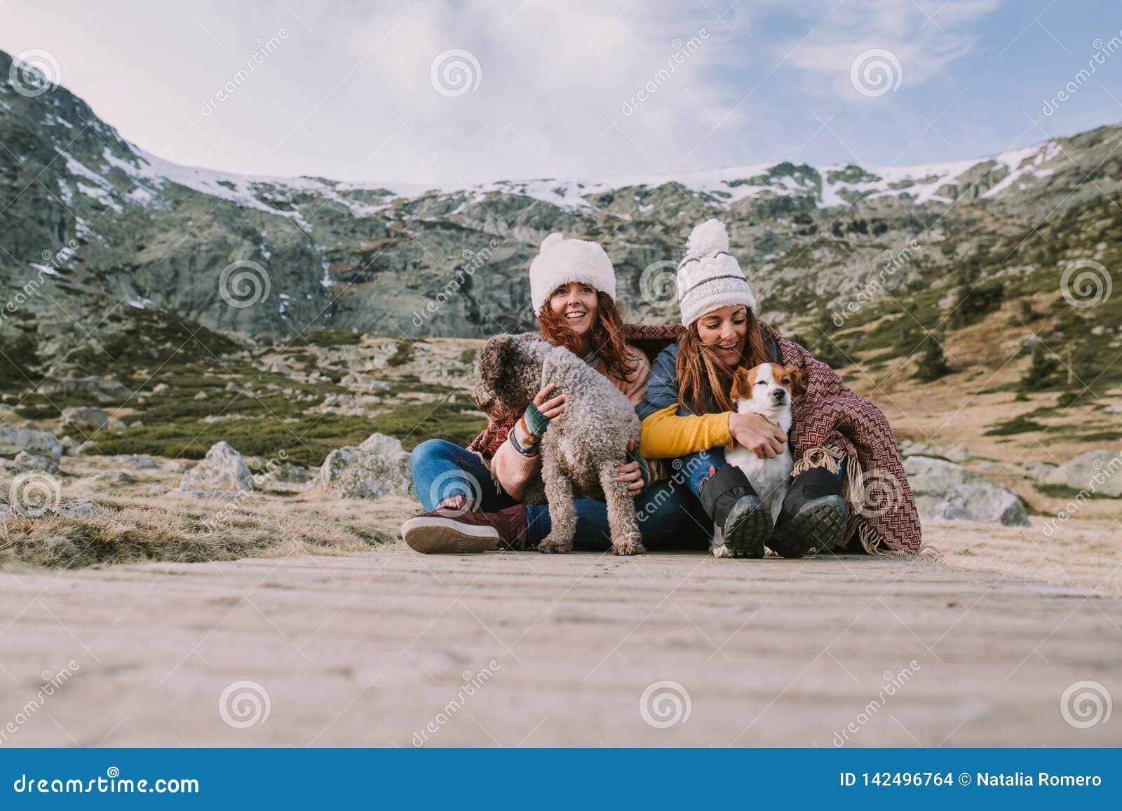 两年轻女人使用与他们的狗在草甸中间