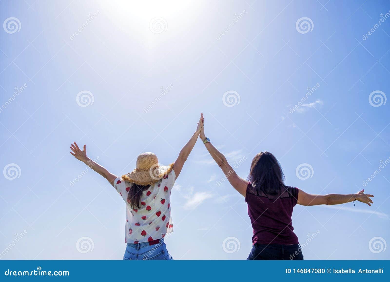 两年轻女人背面图坐有胳膊的篱芭被举反对天空蔚蓝