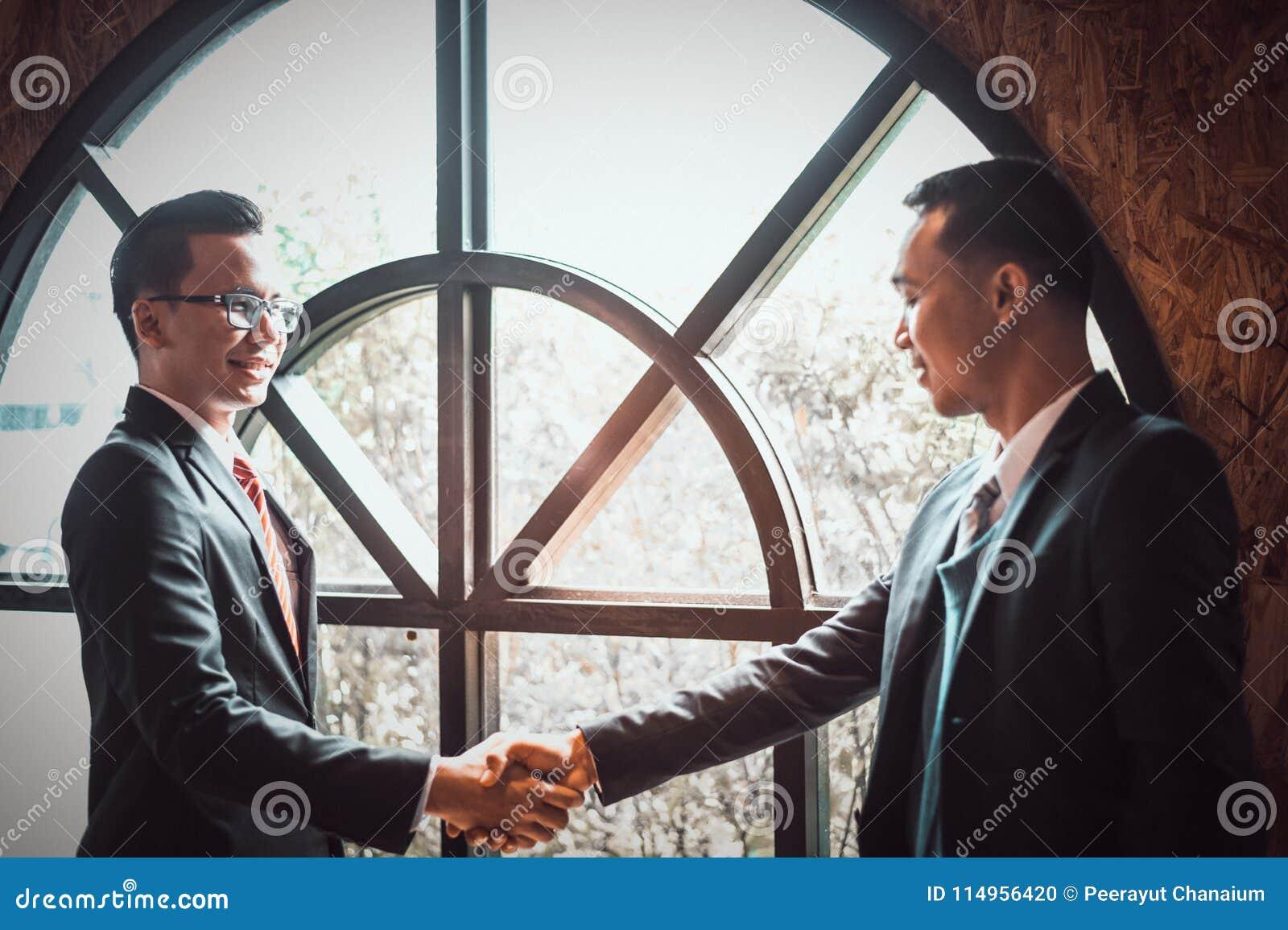 两握手展示的确信的商人他们的协议签协议或合同在他们的公司之间