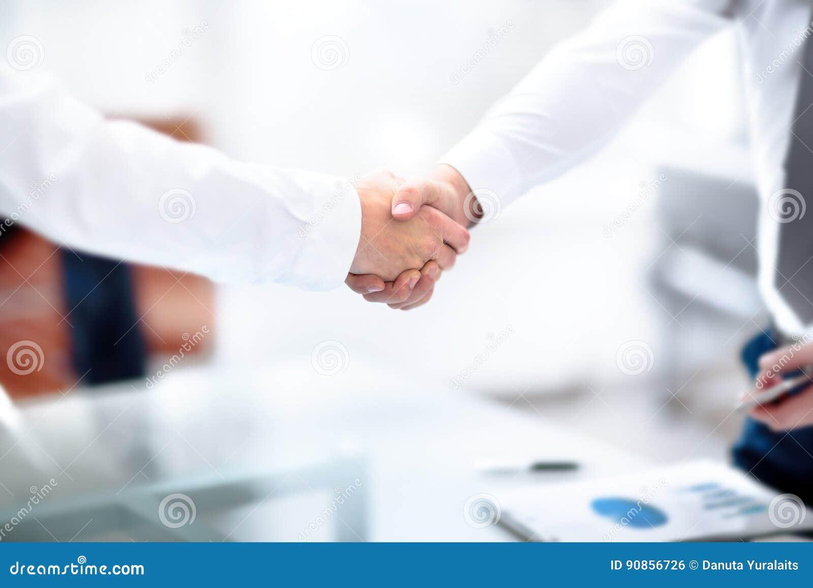 两握手的确信的商人在一次会议期间在办公室,成功,成交,招呼和伙伴概念