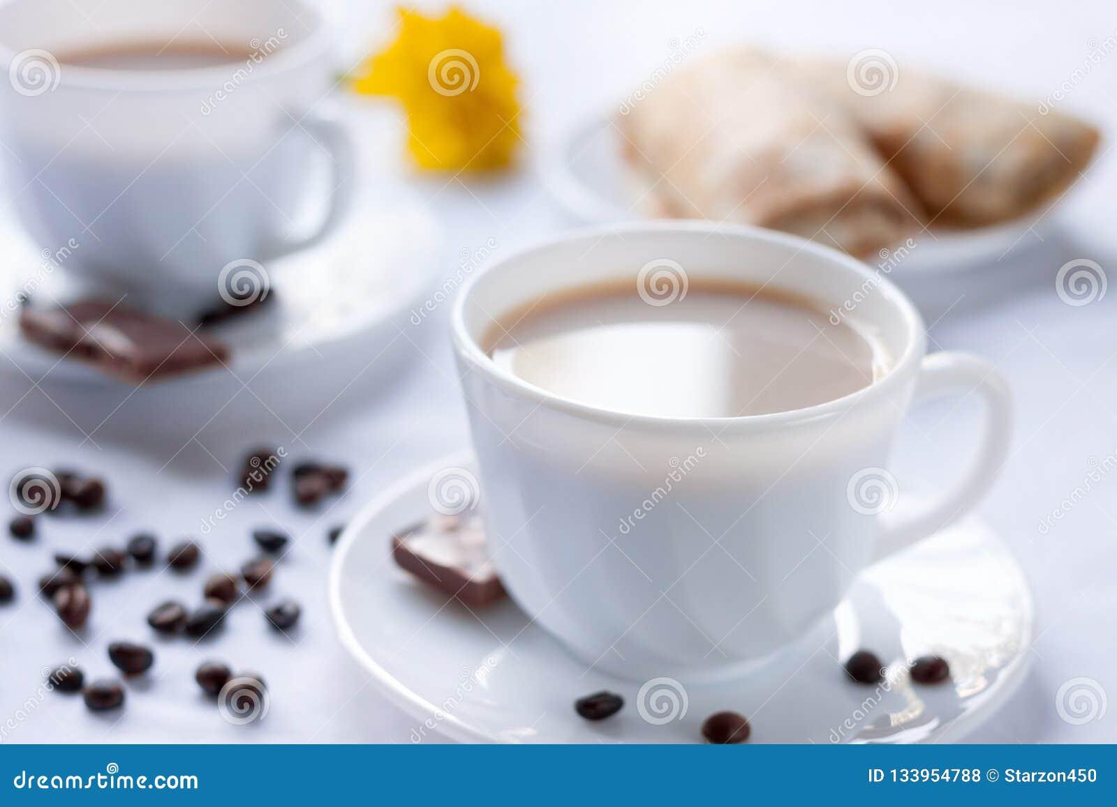 两杯咖啡用牛奶、薄煎饼用果酱和牛奶巧克力 两的早晨早餐
