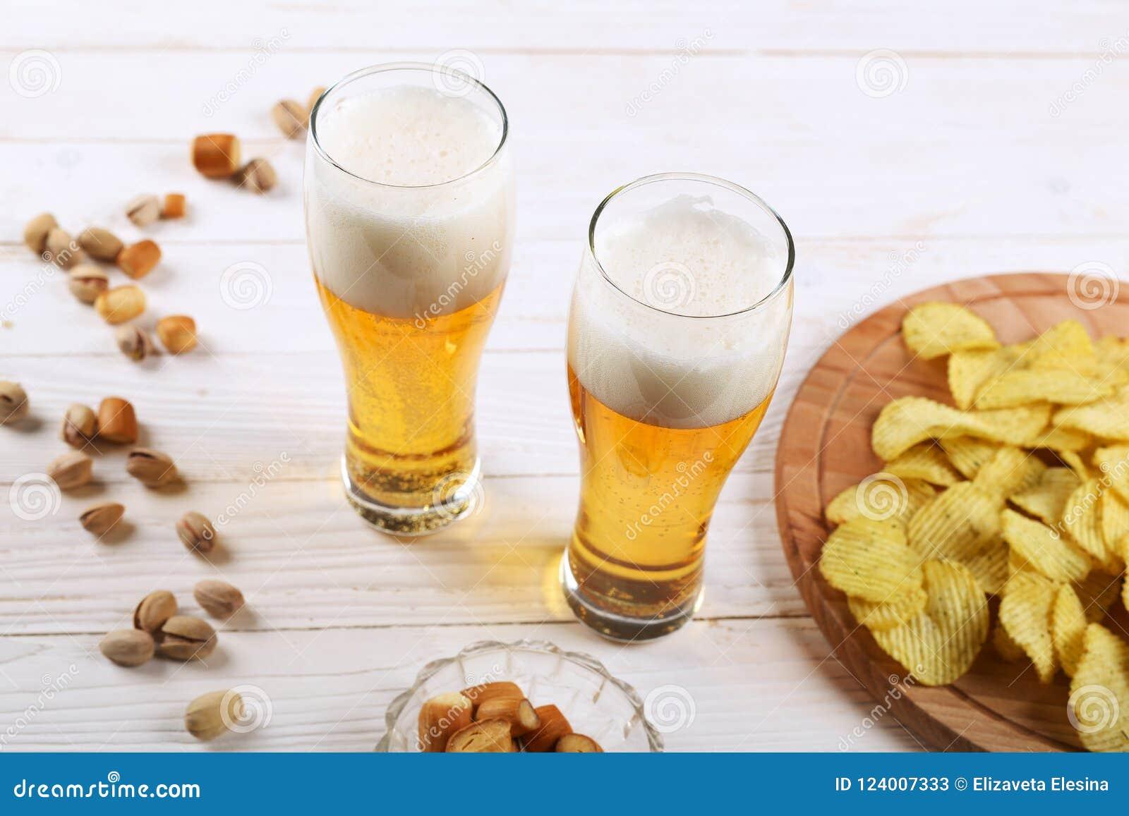 两杯啤酒和快餐在一张白色木桌上 芯片,开心果,干乳酪