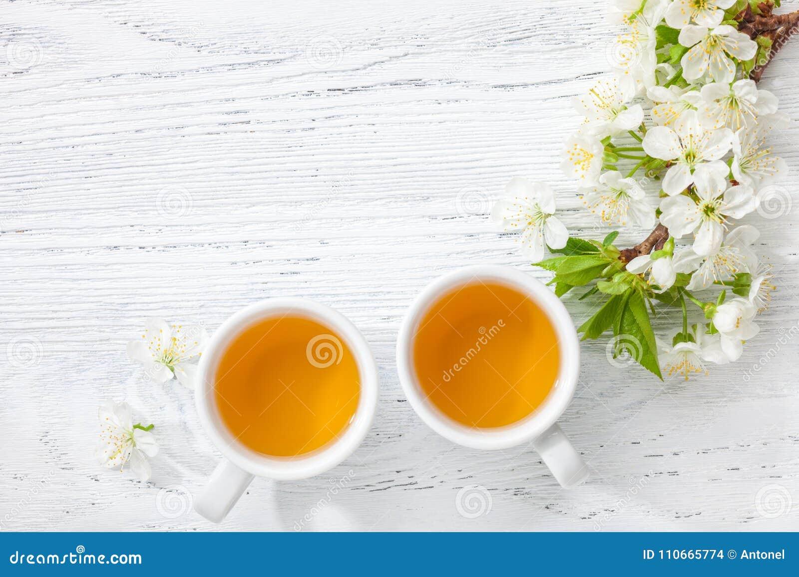 两杯开花樱桃茶和分支在白色木桌上的