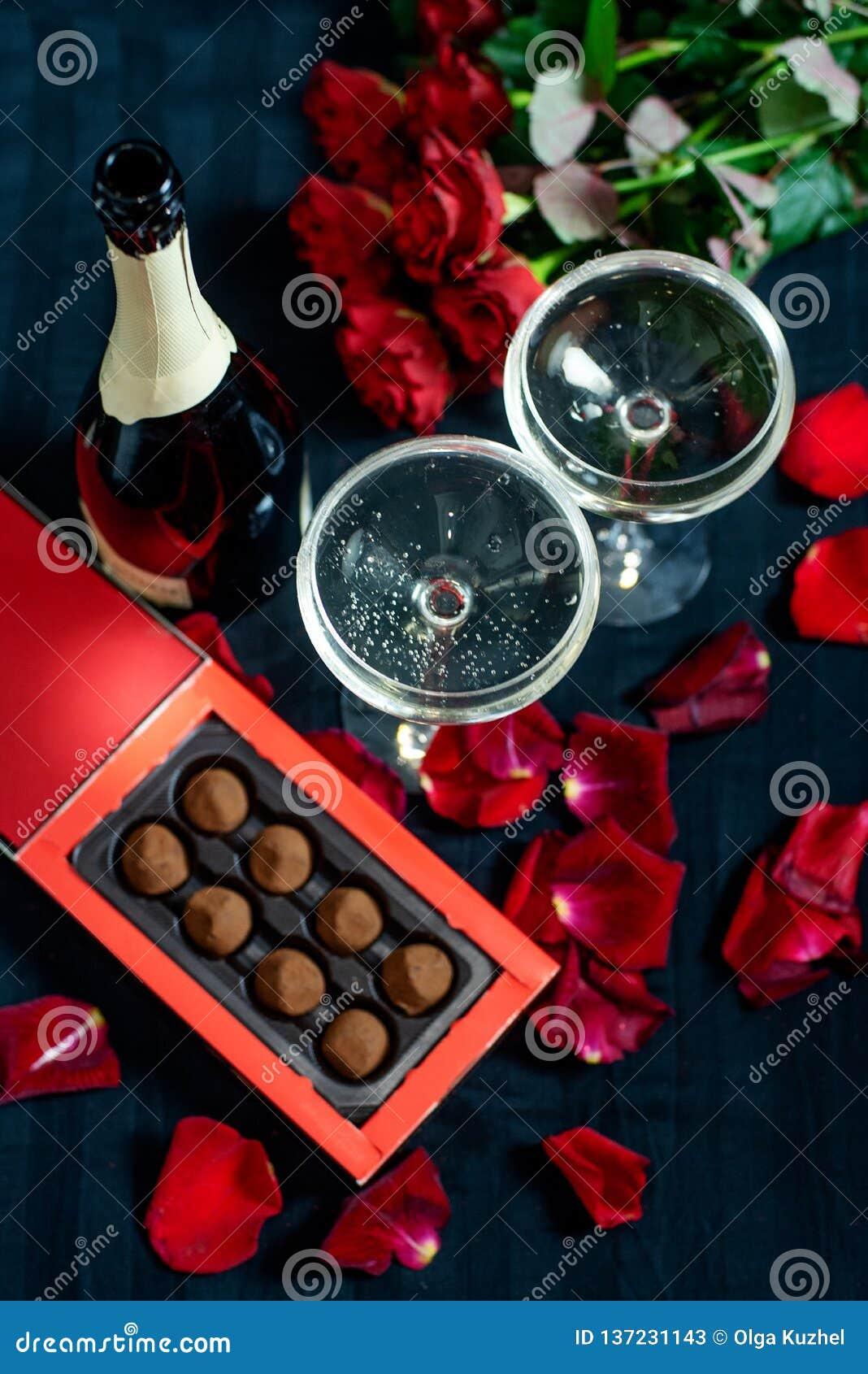 两杯香槟、英国兰开斯特家族族徽、瓣和巧克力在黑背景