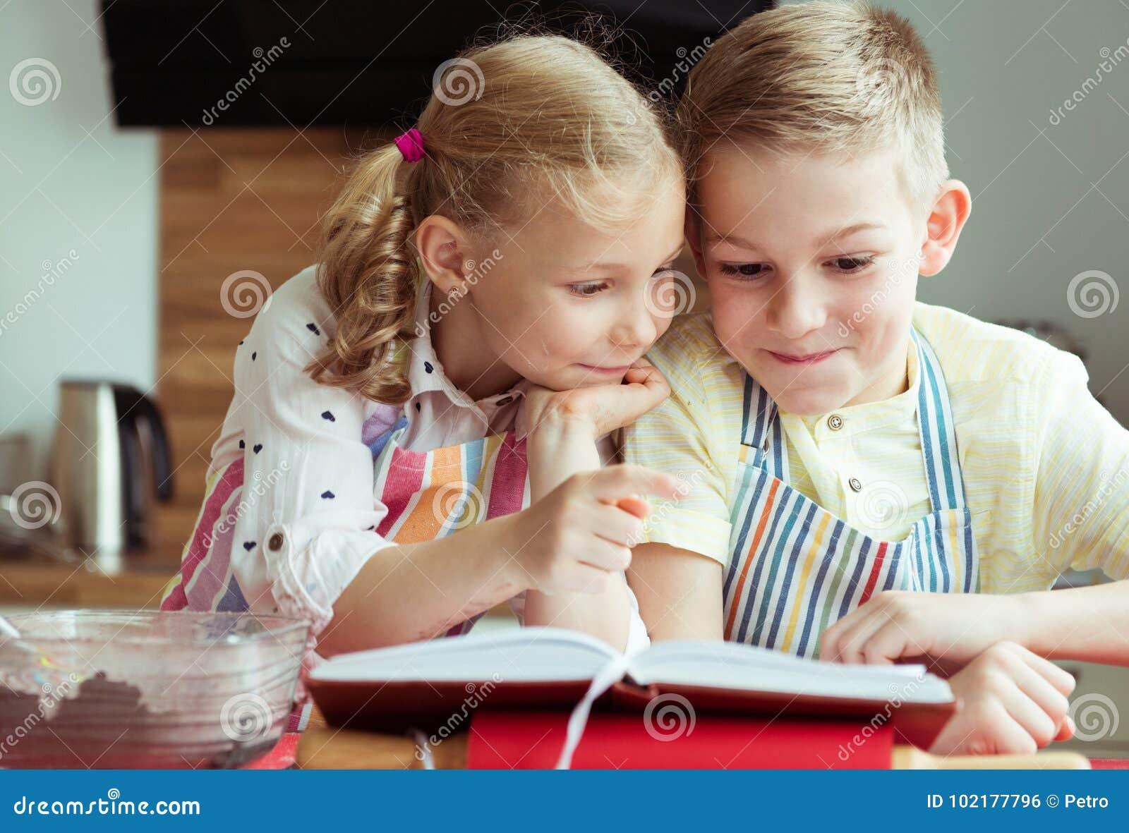 两美丽和探索recept的愉快的孩子在prepari前