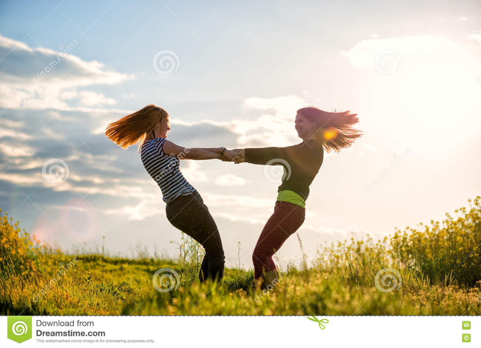 两美丽的女孩获得乐趣一起在日落时间