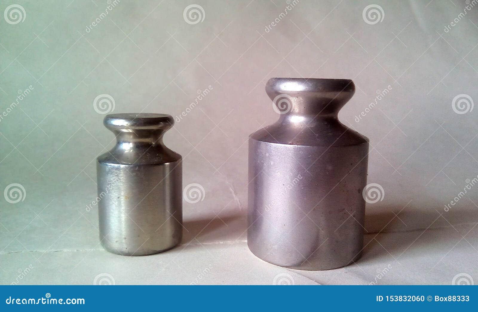 两金属重量特写镜头标度的 在轻的背景的轻的银色金属